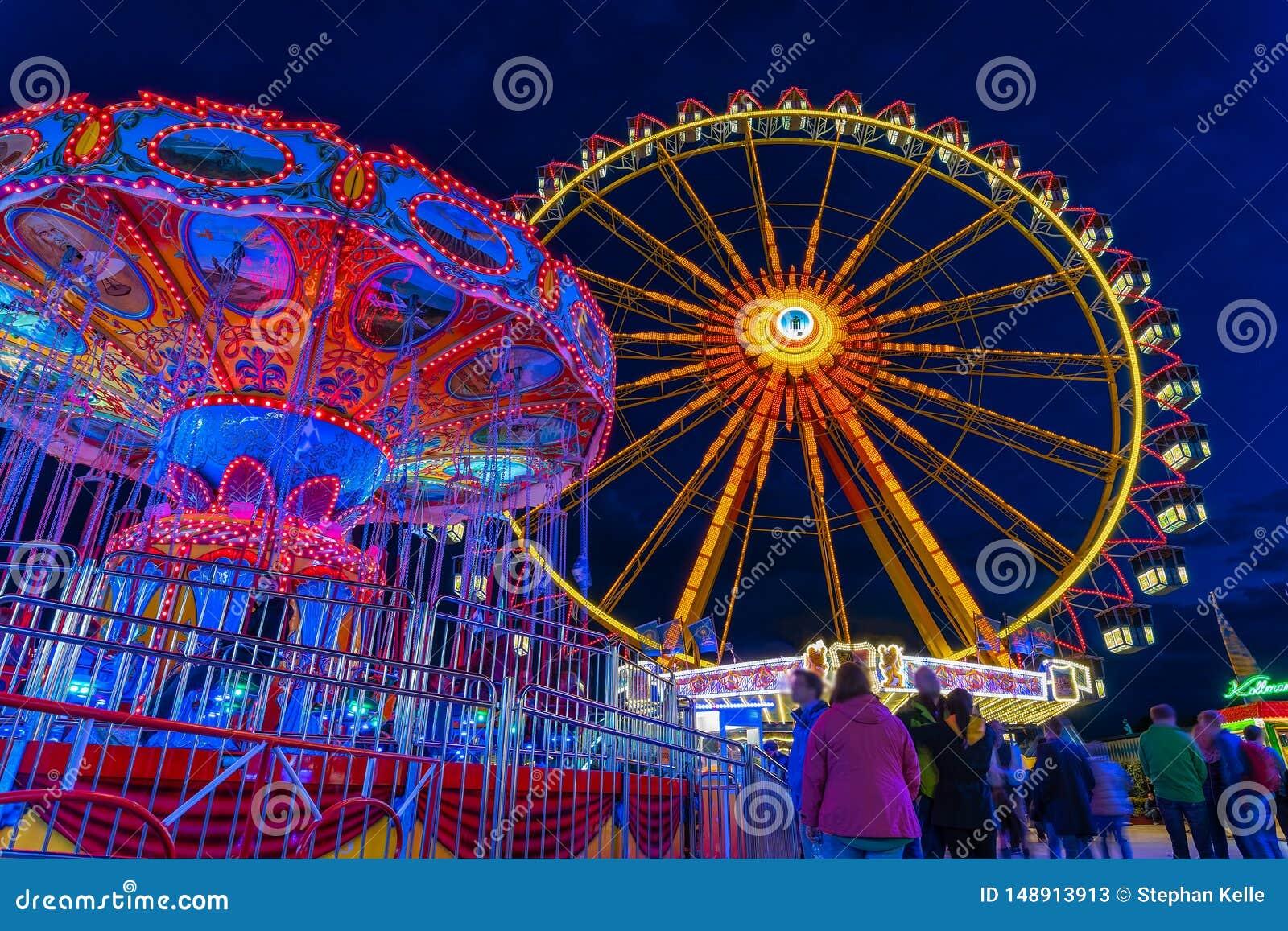 Festival de mola em Munich na hora azul com um carusel iluminado da roda e da corrente de ferris