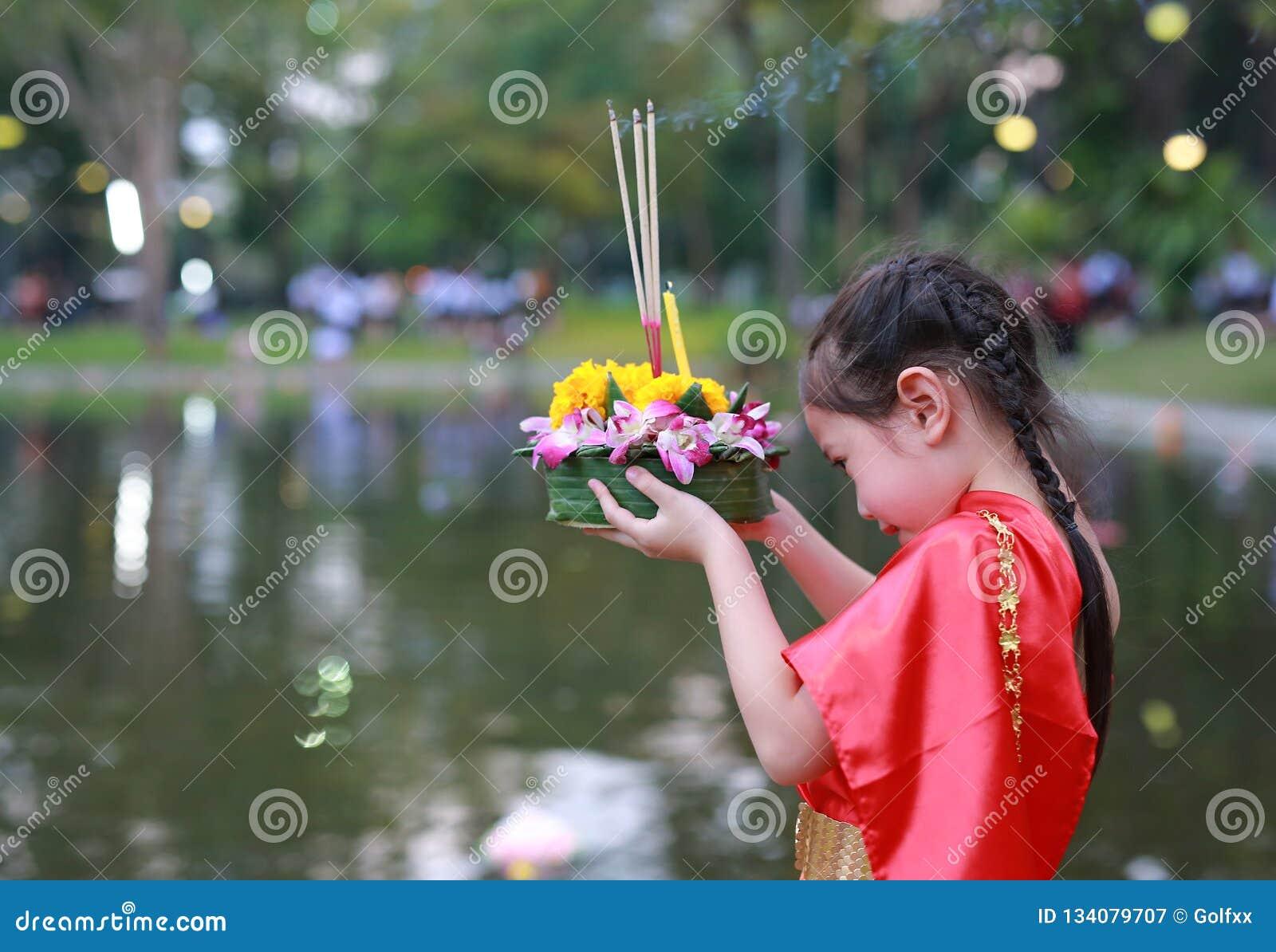 Festival di Loy Krathong, ragazza asiatica del bambino in vestito tradizionale tailandese con il krathong della tenuta per la dea