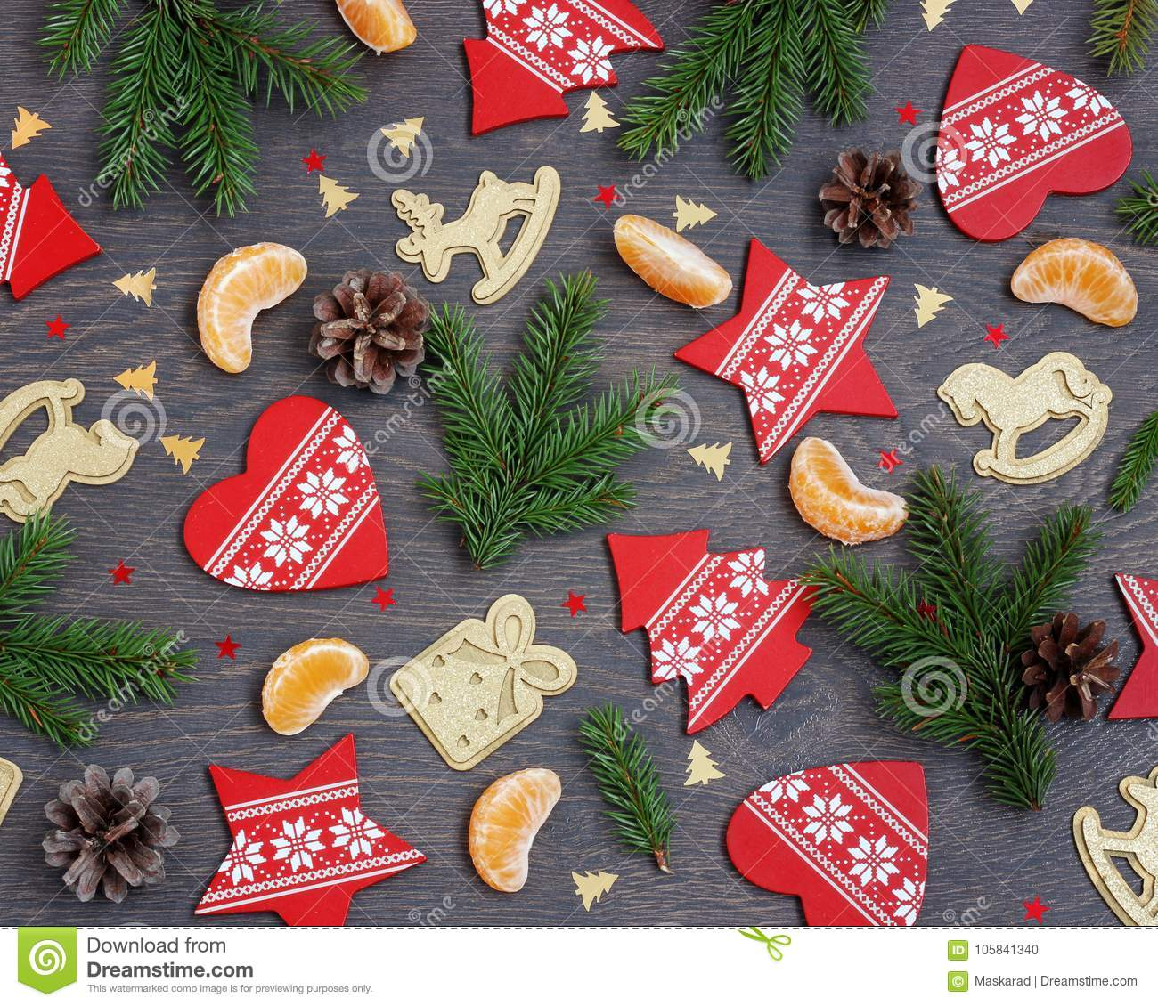 festive background with christmas tree branches segments of mandarins decorations and confetti on a wooden platform the view from the top