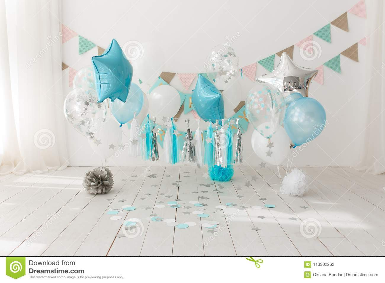 Festive background decoration for birthday celebration with gourmet cake and blue balloons in studio, cake smash first