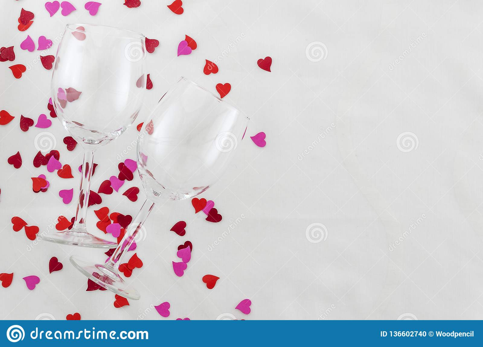 Festive background for Valentine`s day, couple of glasses, white background with hearts, top view