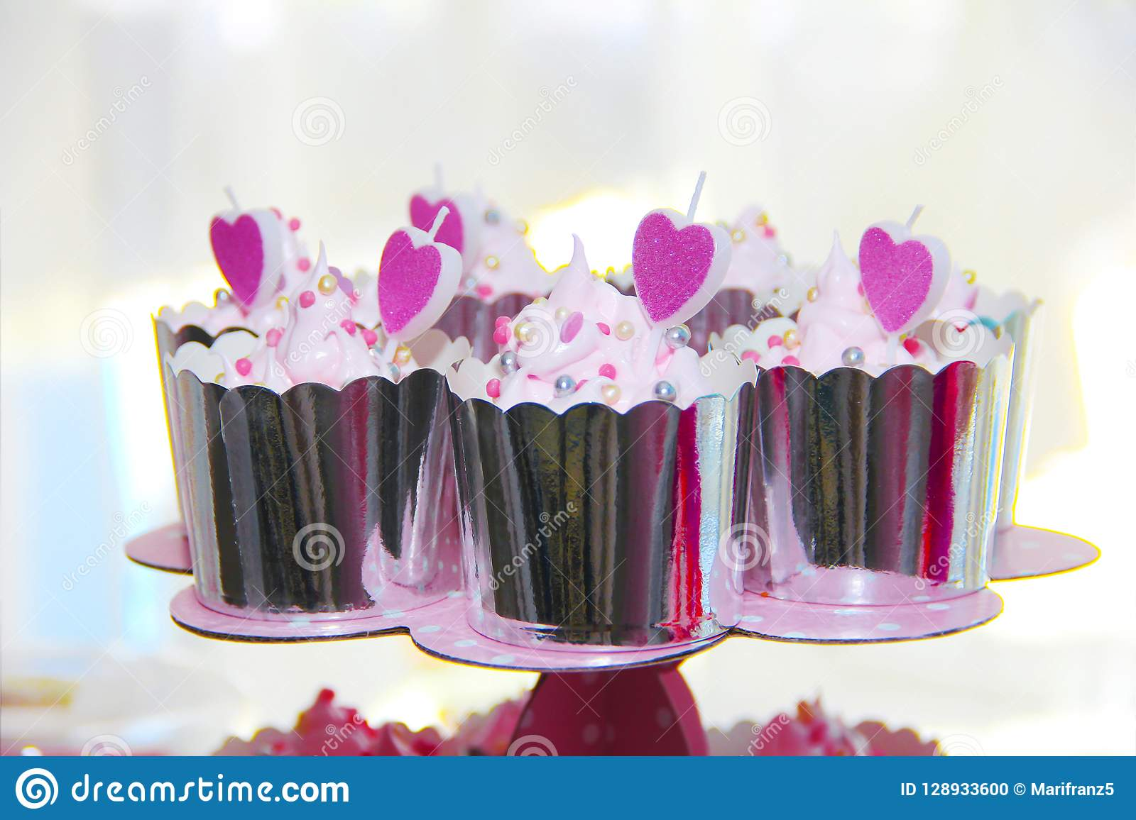 festive cupcakes in a shiny package with decoration in the form of cream and pink hearts