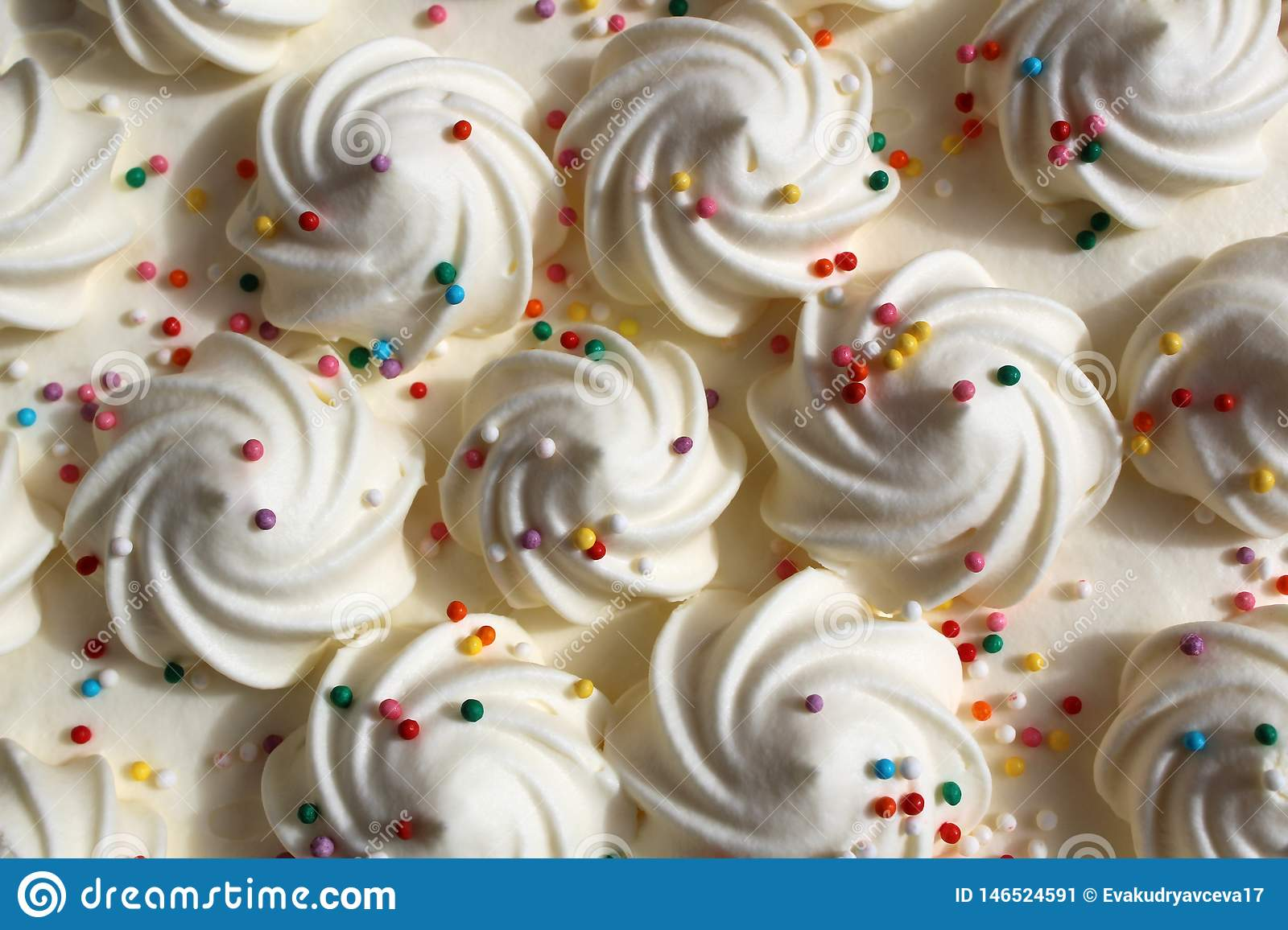 Festive curls for white cream cake with multicolored sprinkles