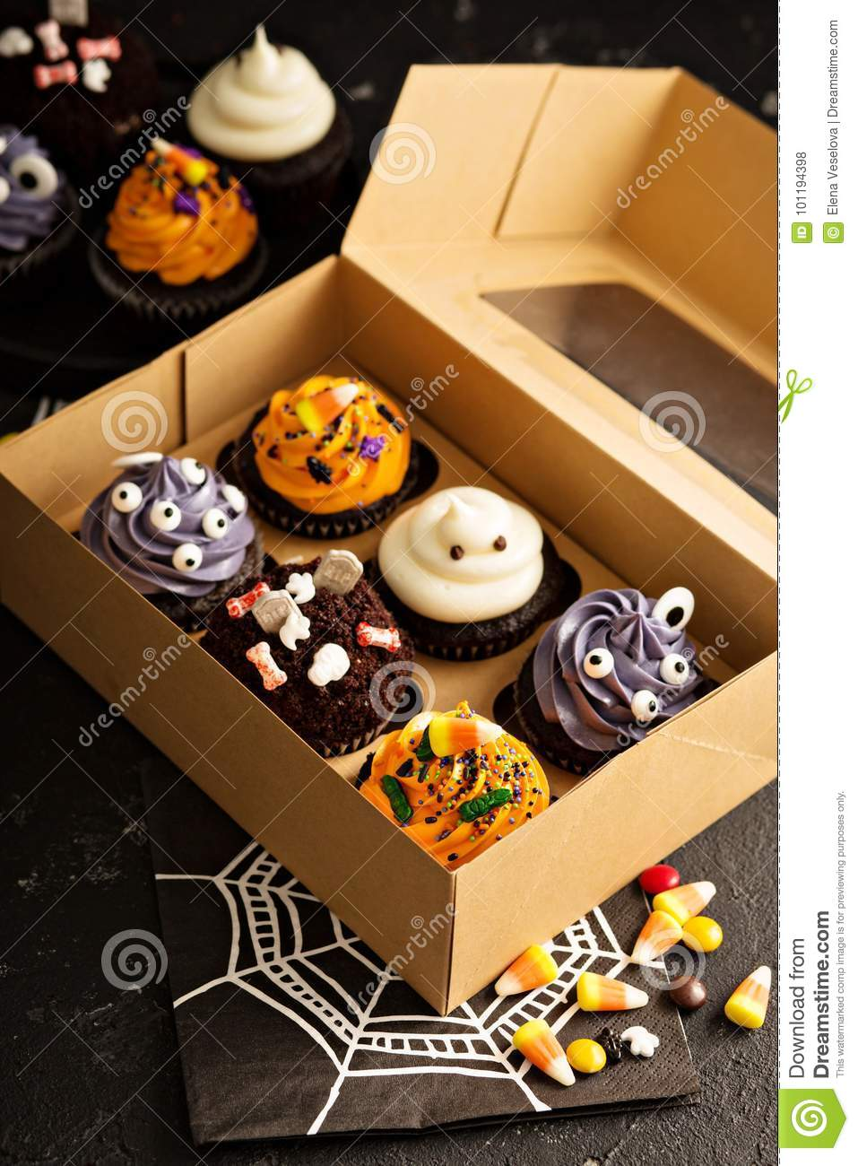 set of festive halloween cupcakes and treats decorated with sprinkles and candy in a box