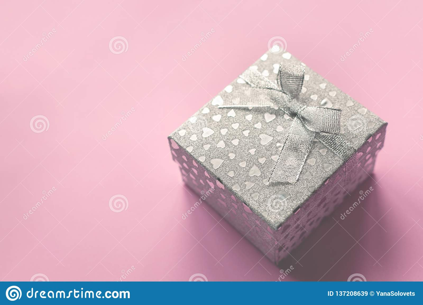 Silver gift box on a gentle pink background. Beautiful background for all holidays