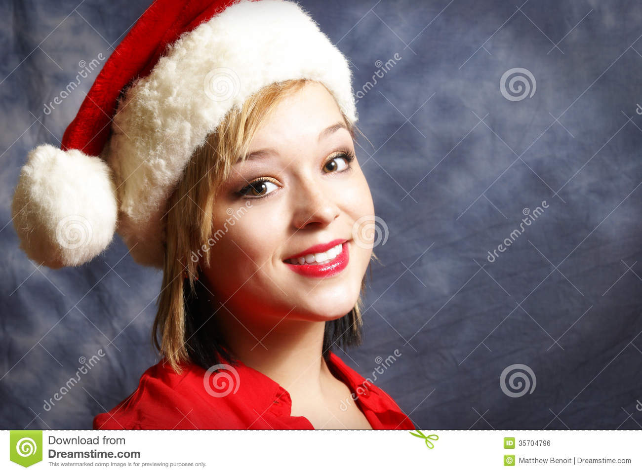 A Happy Young Woman Wearing A Santa Hat For The Spirit Of Christmas