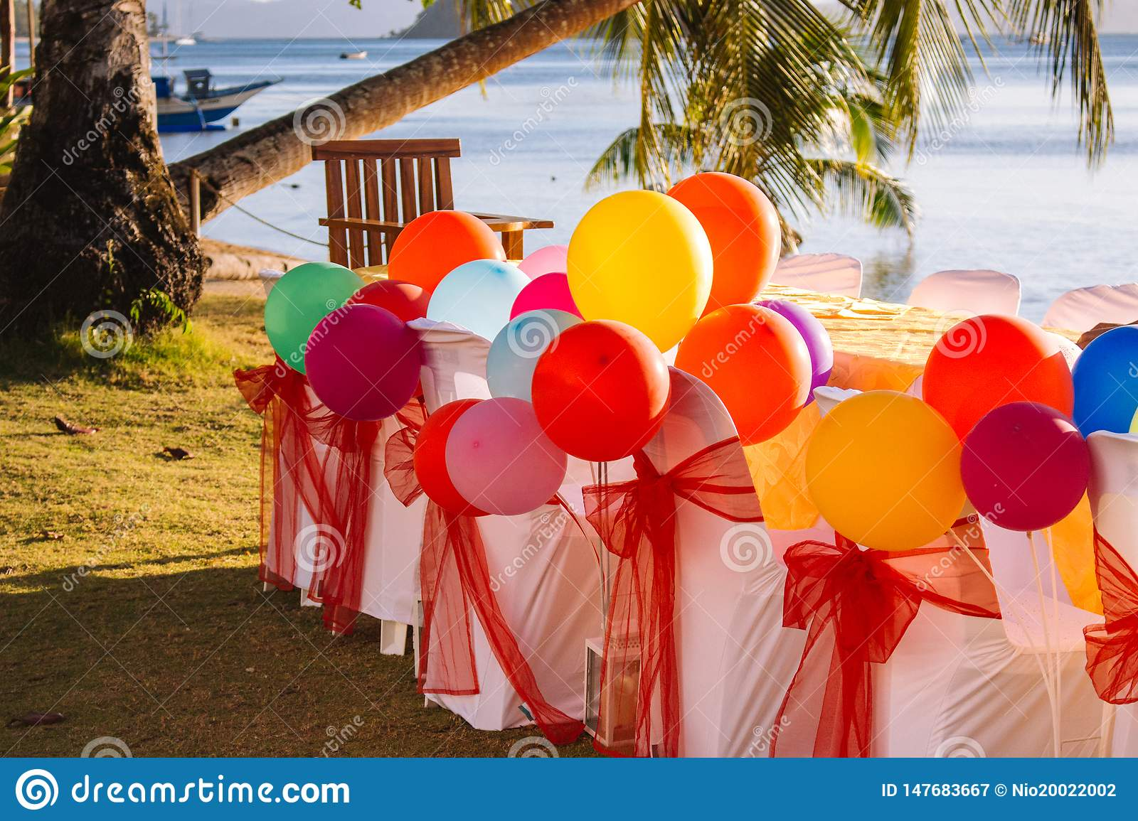 Festive table with colorful balloons on beach background with palm tree and boat. Happy birthday celebration concept.
