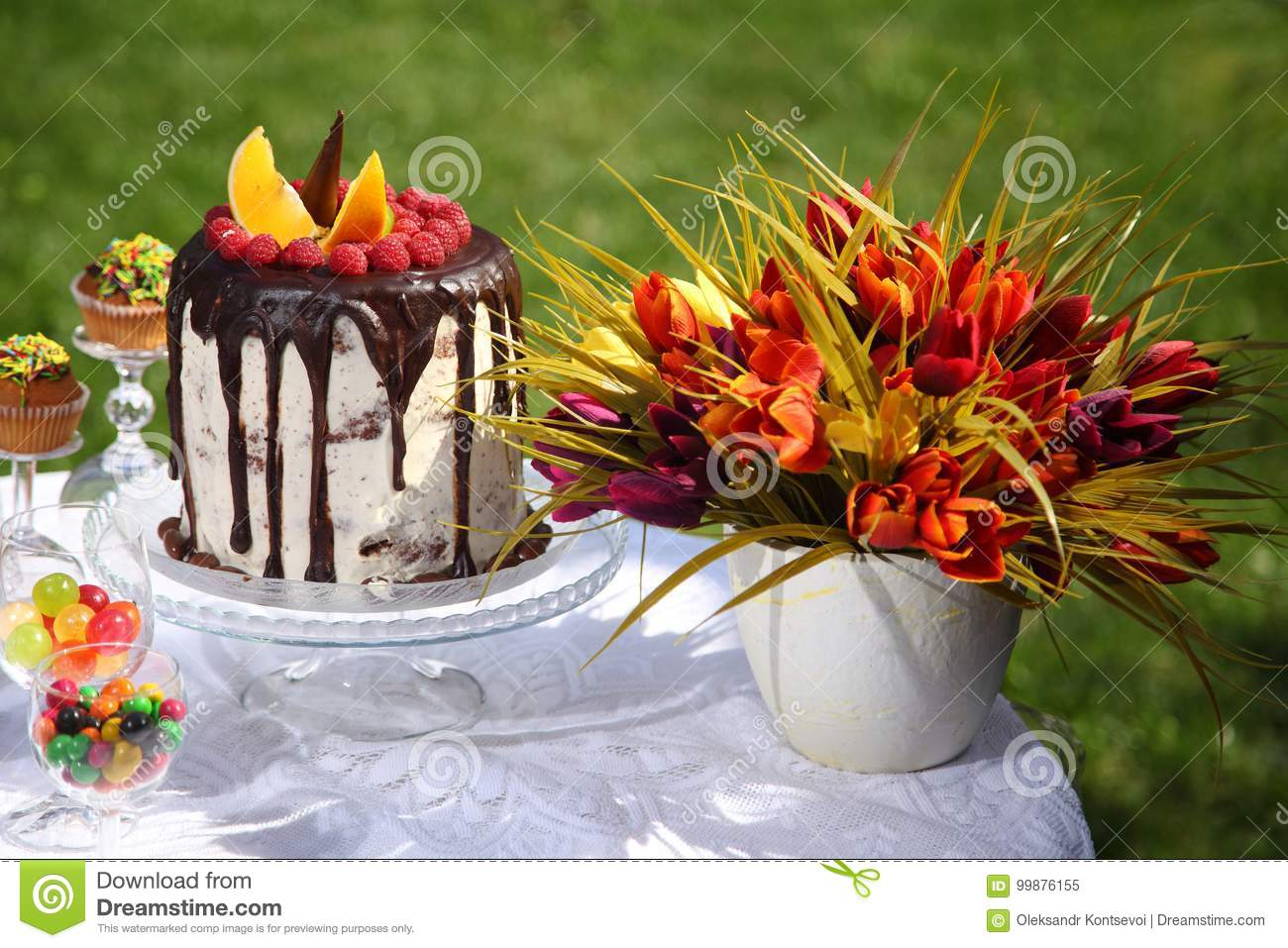 A Festive Table Decorated With Birthday Cake With Flowers And Sweets