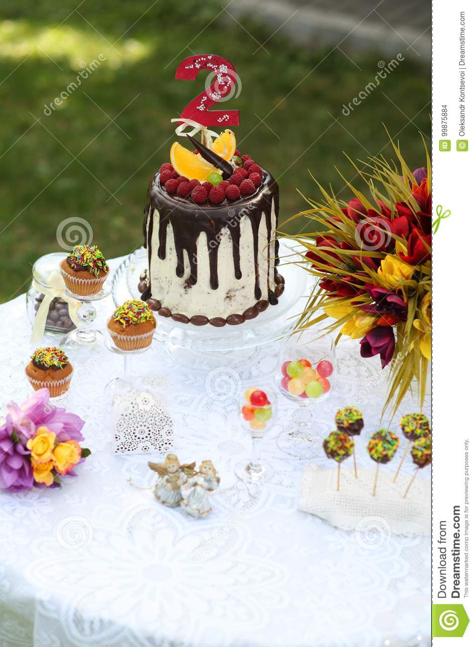 A Festive Table Decorated With Birthday Cake Flowers And Sweets
