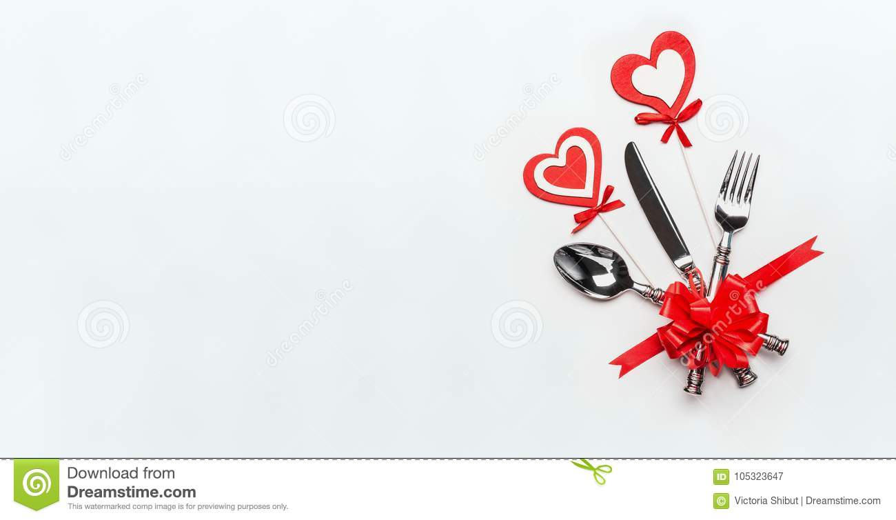 Festive table place setting with cutlery and red ribbon and hearts on white background, banner.