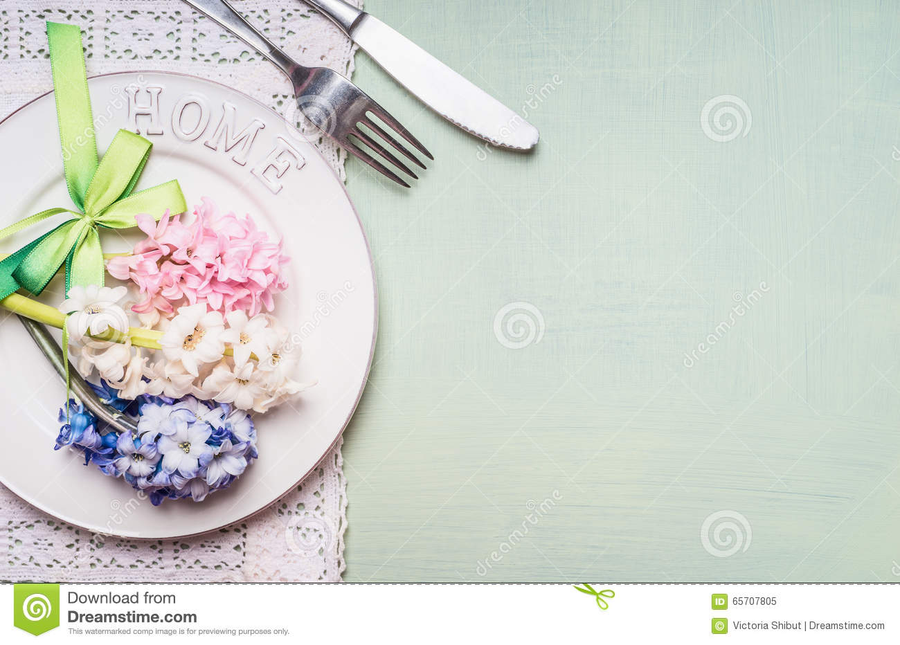 Festive table place setting with hyacinths flowers decoration, plate, fork and knife on light green background, top view