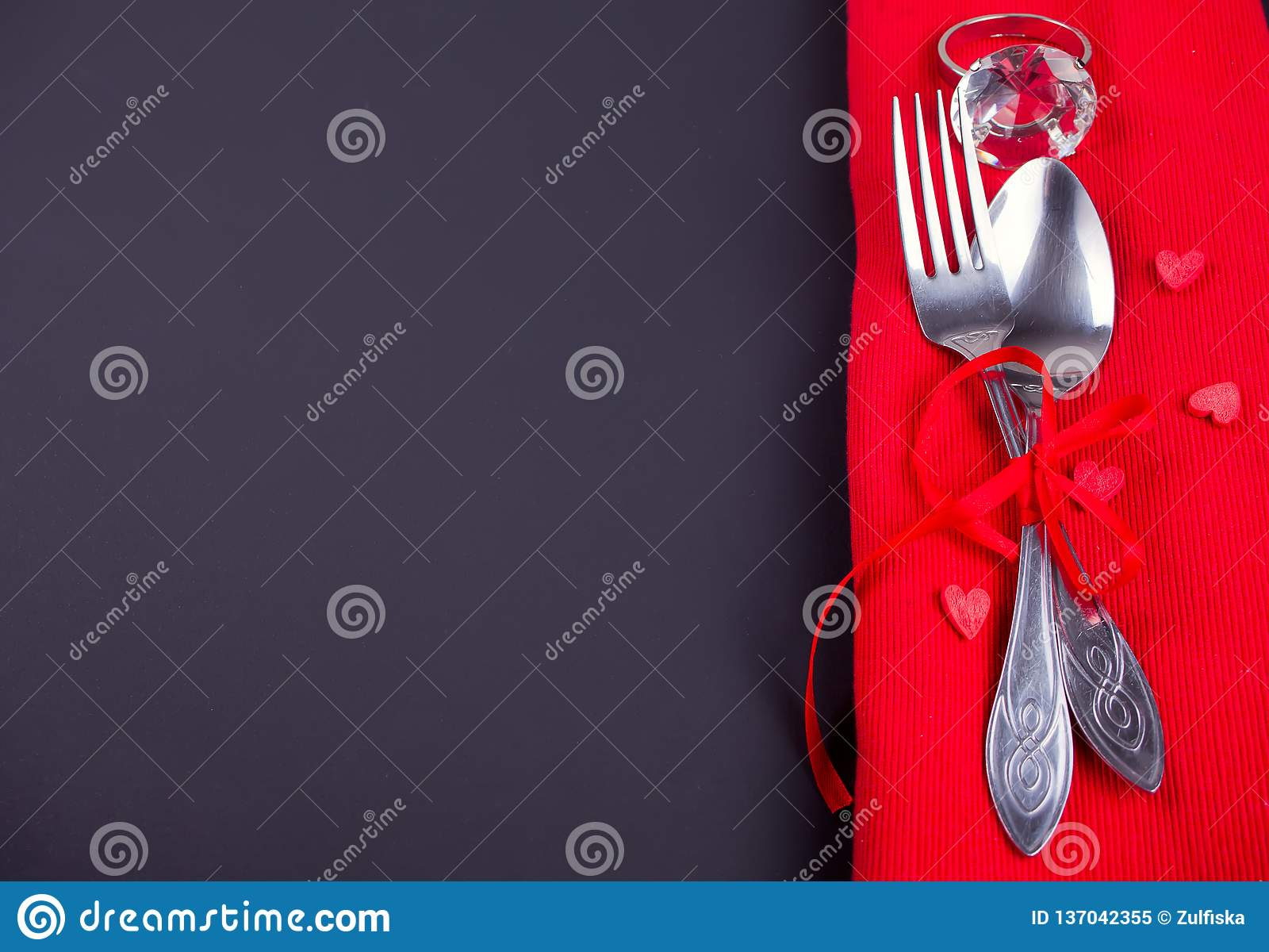 Festive table setting for Valentines Day with red napkin and cutlery. Copy space. Top view