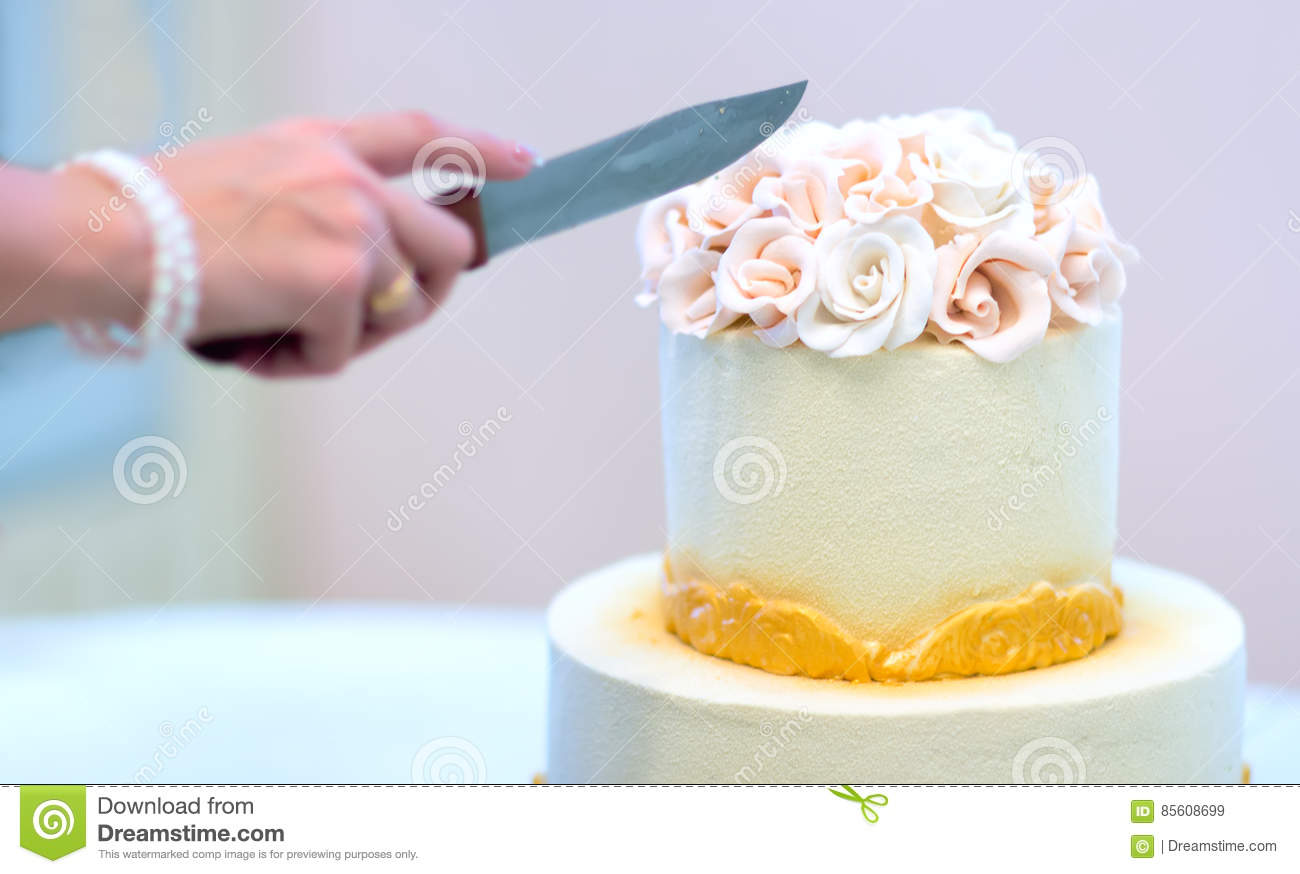 Festive wedding cake with flowers, yellow-orange flowers, bunk, beautiful, gentle, the bride cuts the cake