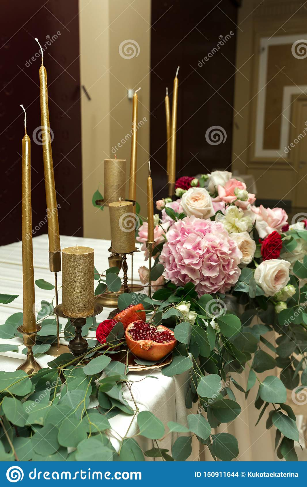 Festively dekorerad banketttabell i restaurangen Nya blommor ?r guld- stearinljus och r?da stolar och granatr?tt dyrt rikt