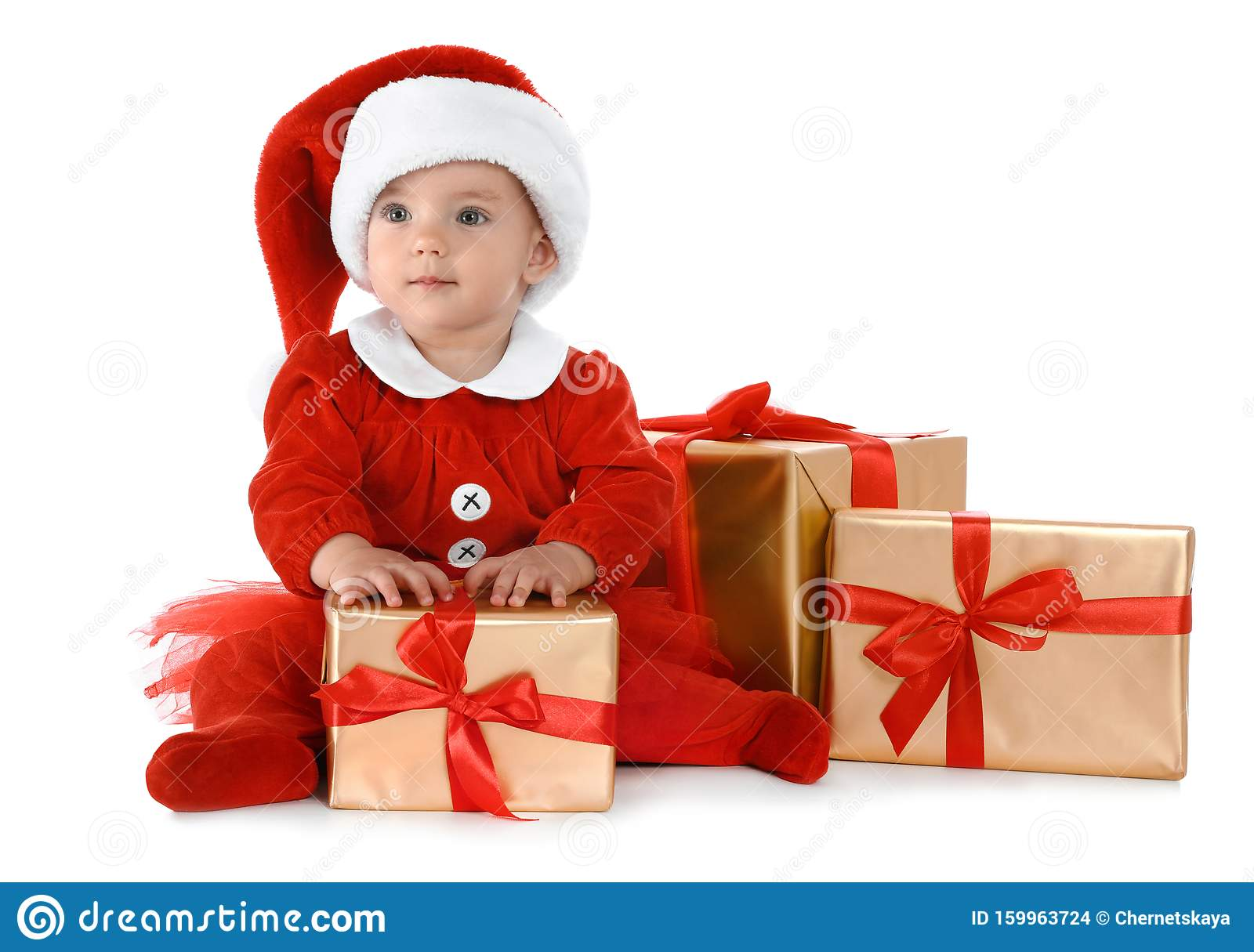 Festively dressed baby with gift boxes. Christmas celebration