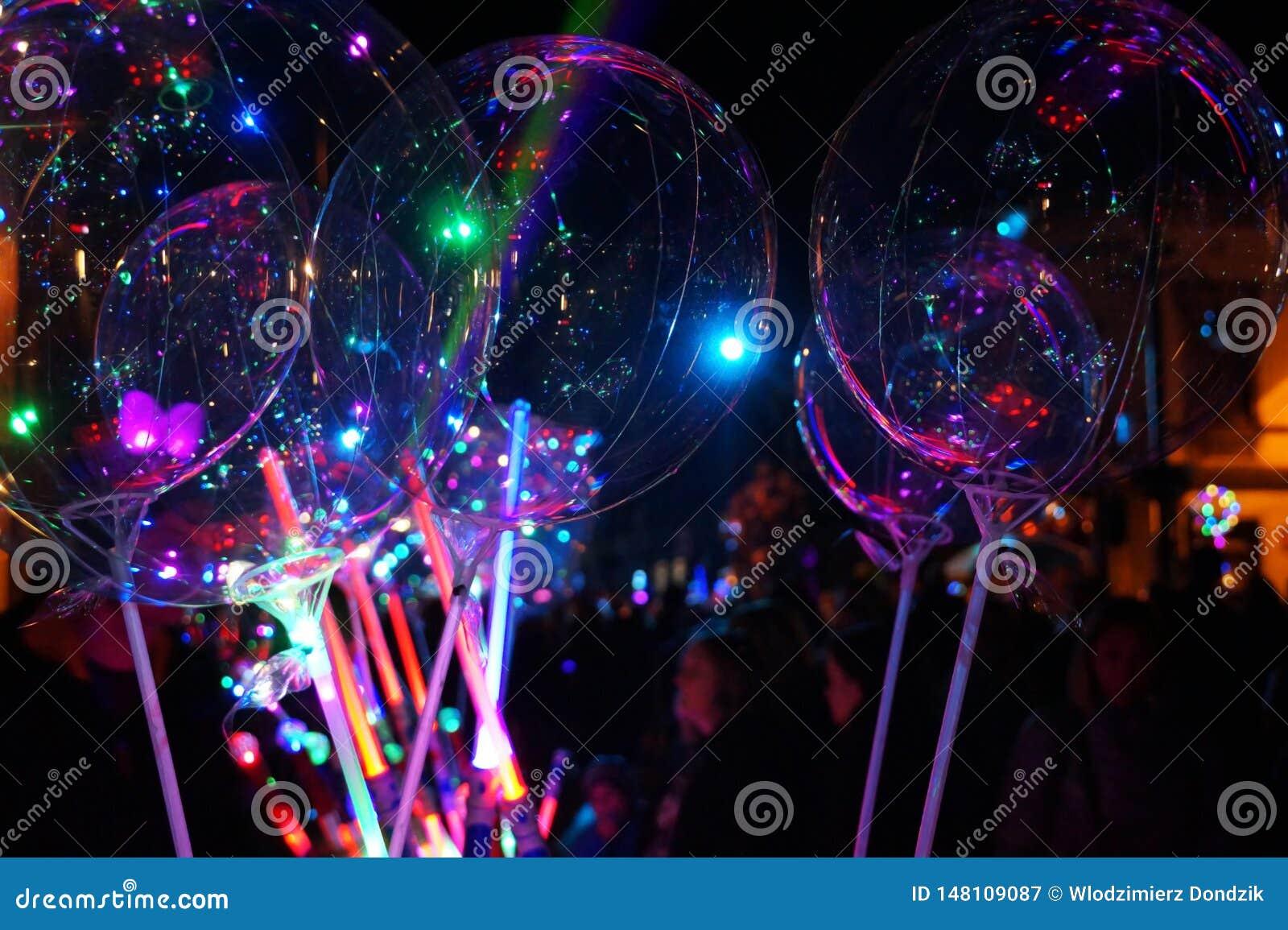 Festiviteiten bij nacht Een tribune die lichtgevend speelgoed verkopen: ballons en zwaarden
