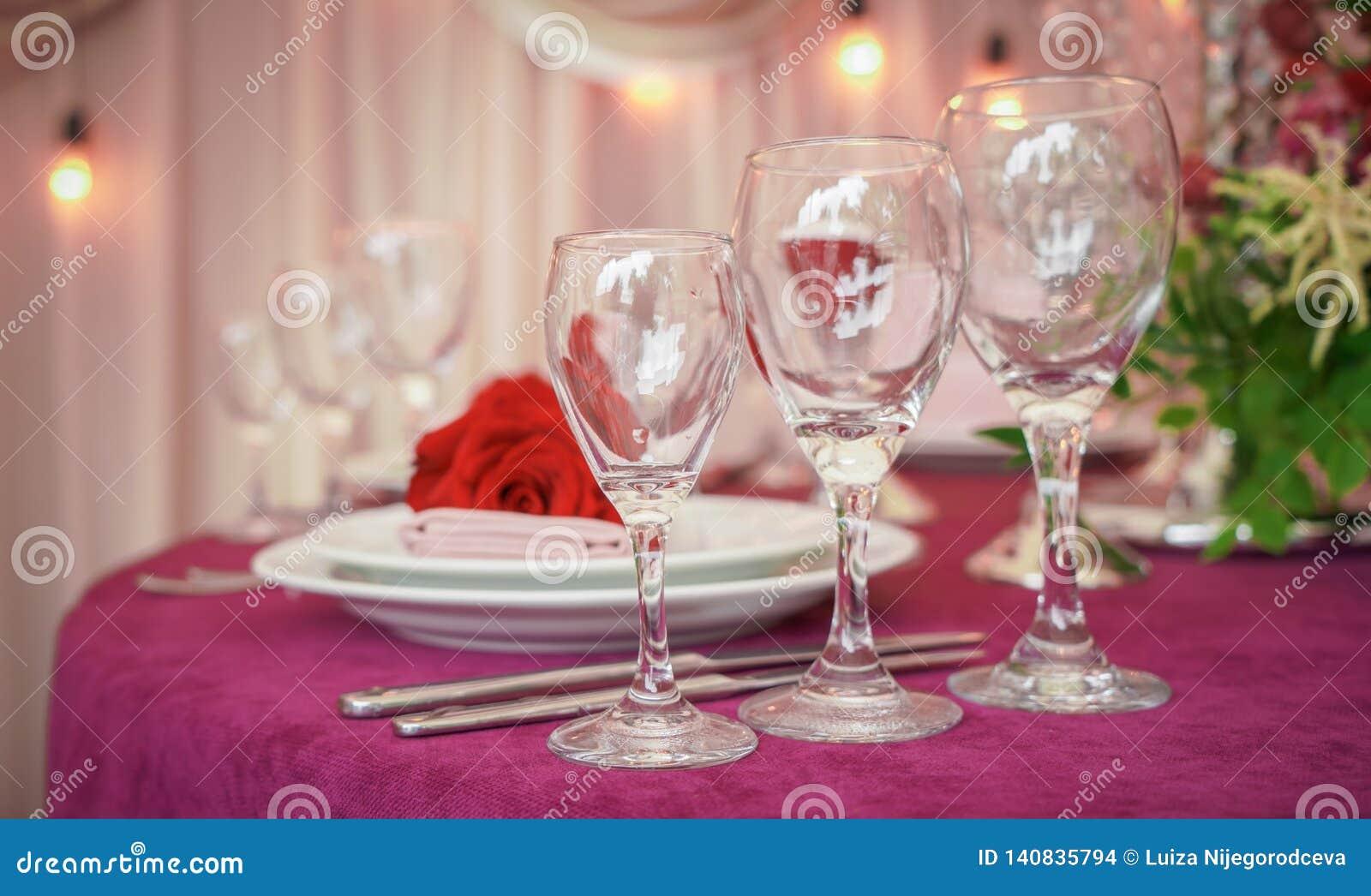 Festliche Hochzeitstafeleinstellung mit roten Blumen, Servietten, Weinlesetischbesteck, Gläsern und Kerzen, heller Sommertabellen