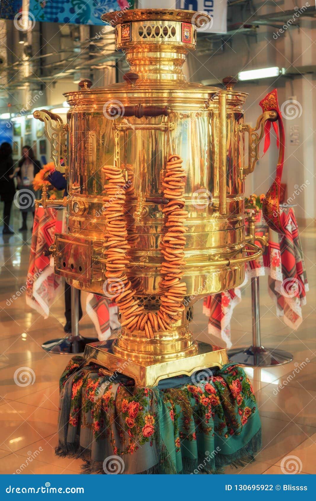 Festlicher russischer Samowar der großen glänzenden goldenen Weinlese mit einem Bündel Bageln dargelegt im olympischen Mediacente