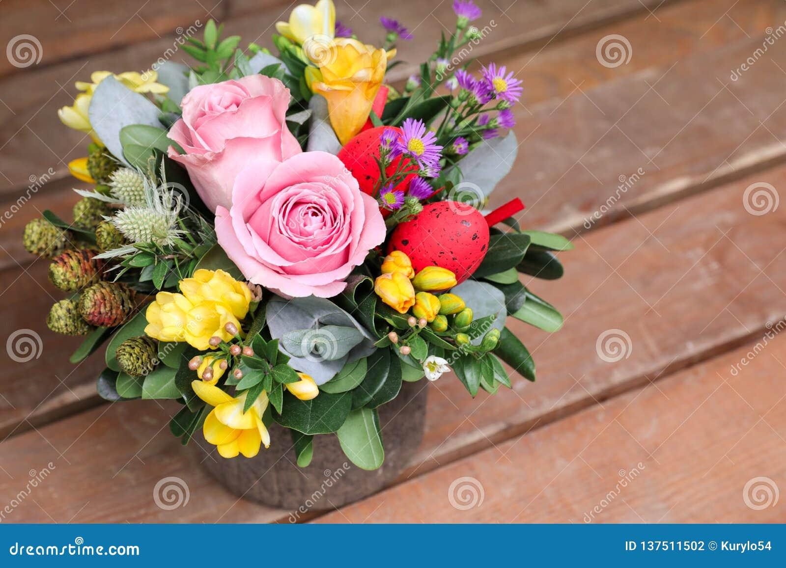Festlig blommaordning av rosa rosor, gula freesiablommor, eukalyptussidor och andra växter med röda påskägg