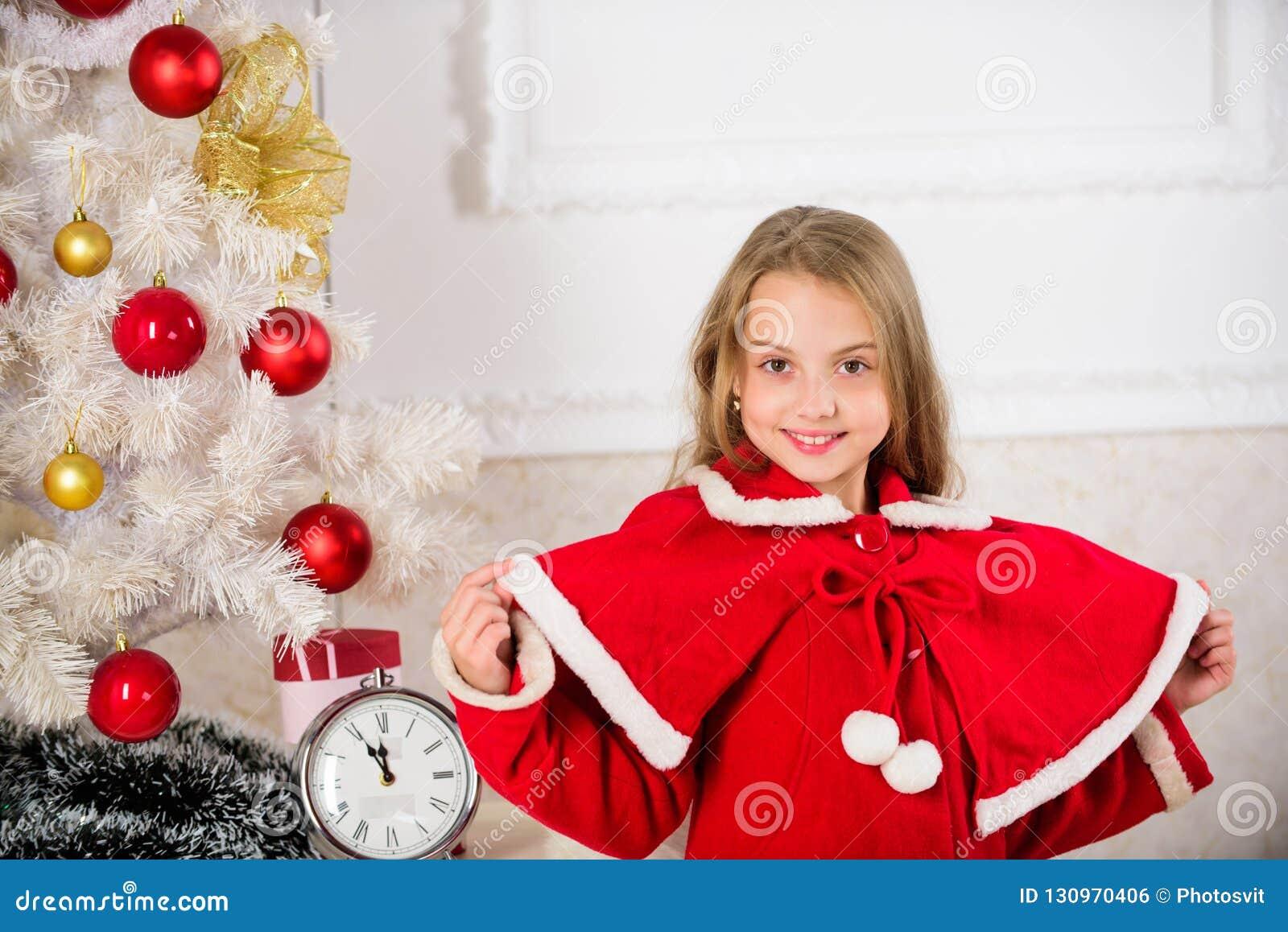 Festlig dräkt för ungeflicka nära julträd Barndomlyckabegrepp Barnet firar jul hemma favorit