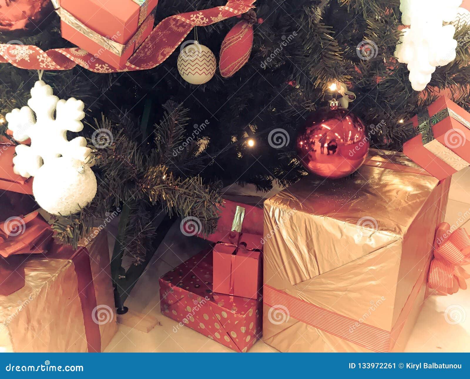 Festliga färgrika härliga skinande gåvaaskar, garneringar under det gröna trädet för jul med visare och filialer, leksaker