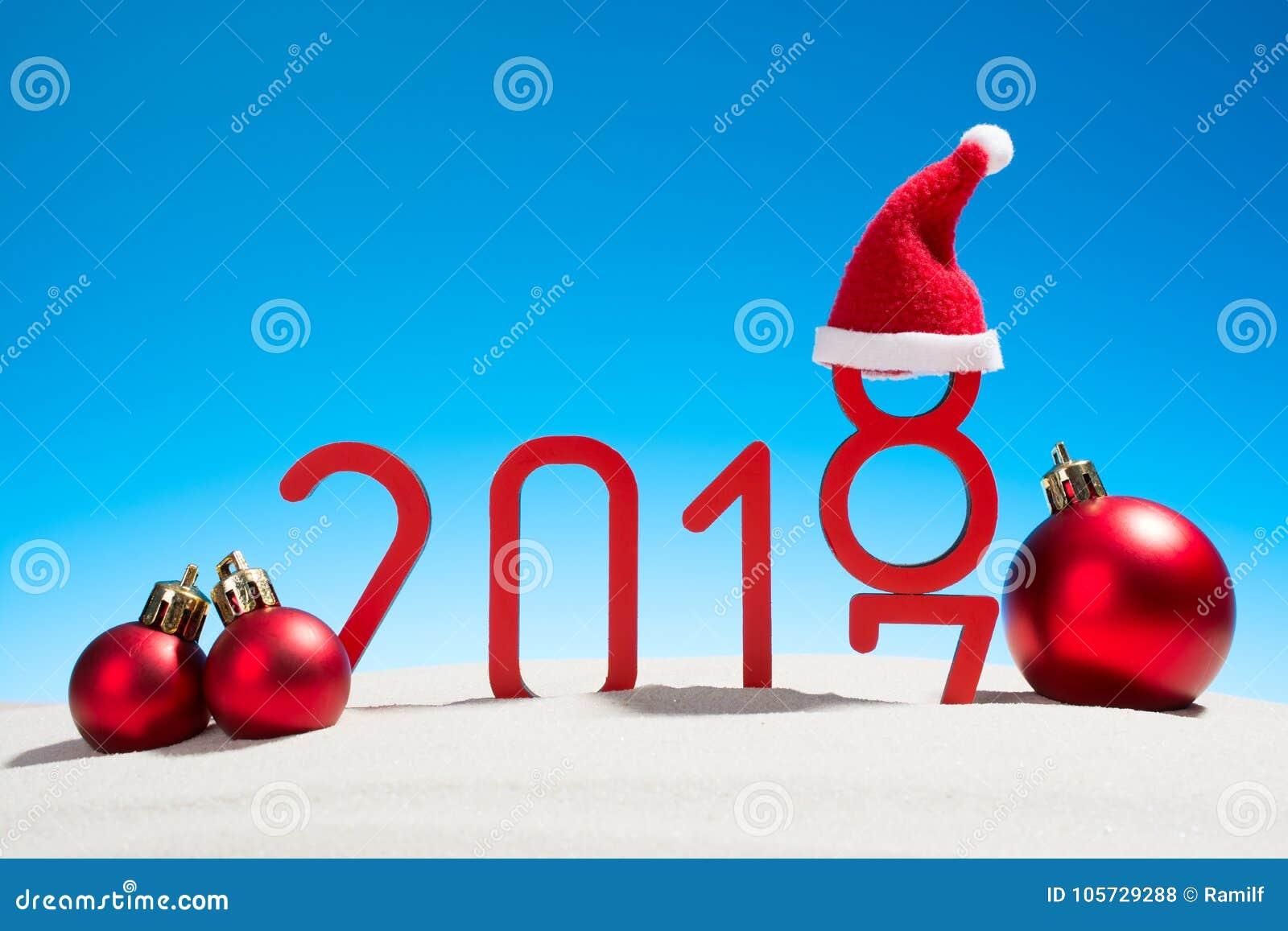 Festliga nya år begrepp med jul klumpa ihop sig på en solig tropisk strand med det ändrande datumet 2017 - 2018 i röd och kopieri