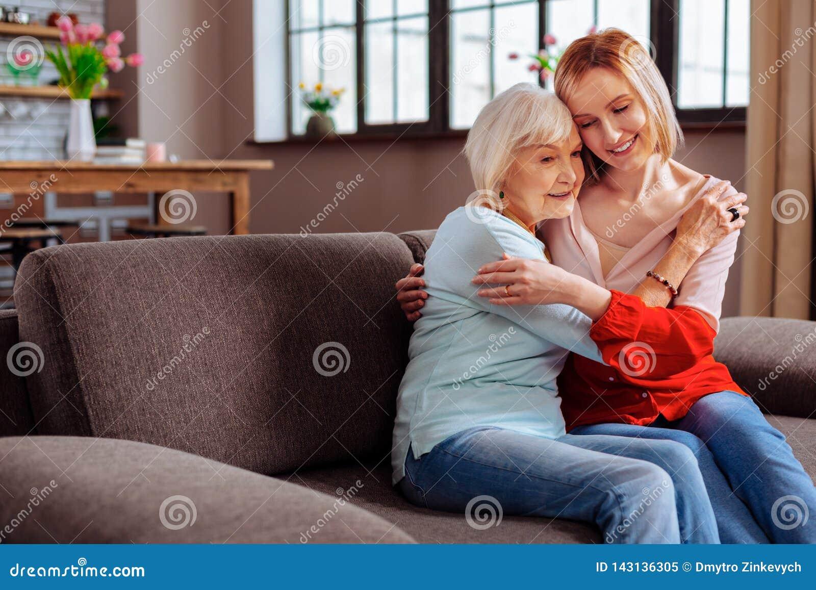 Festnehmend Frau die im Ruhestand, die fest Enkelin umfasst, kommen Sie, sie zu besuchen