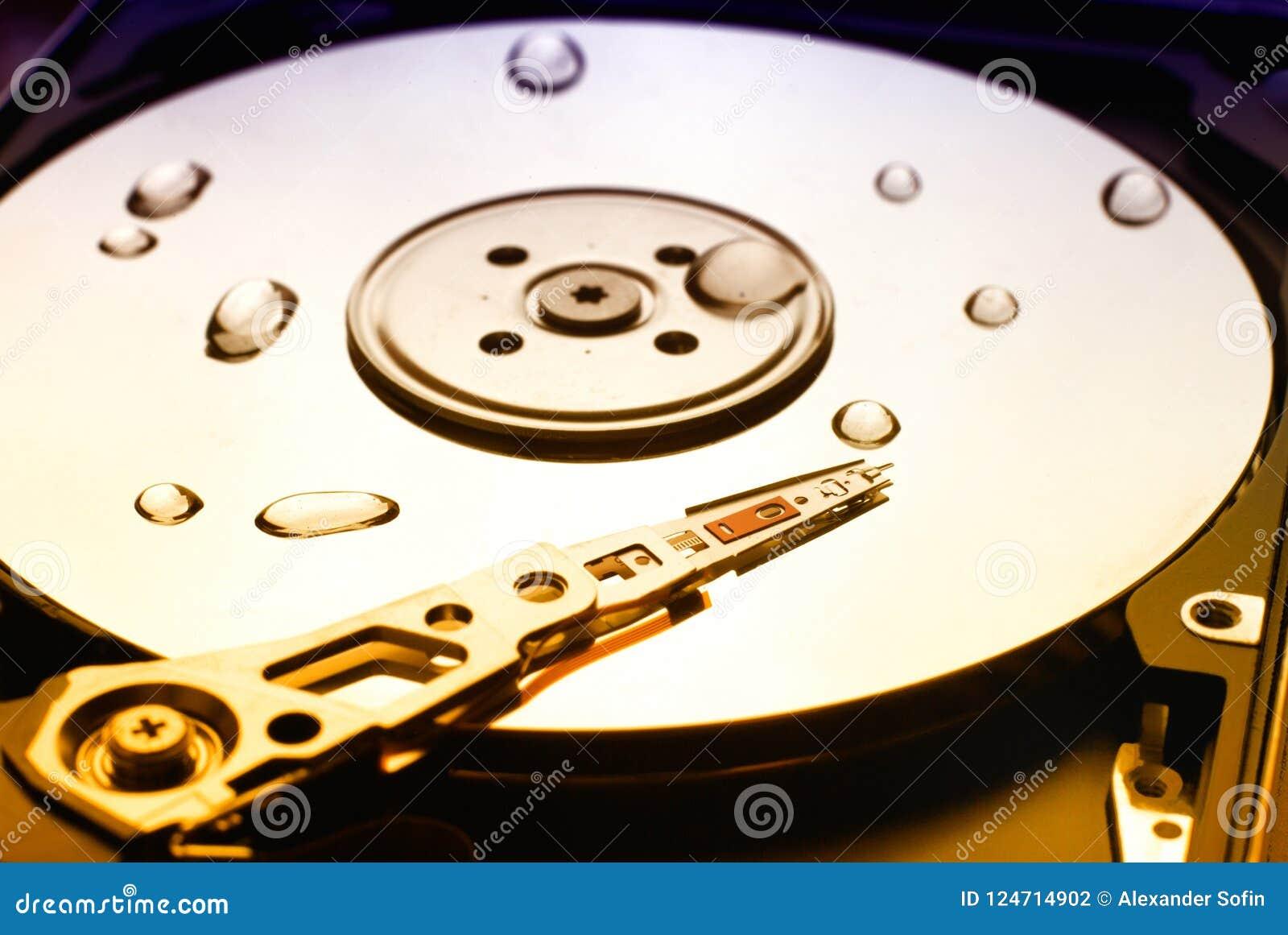 Festplattenlaufwerk des Computers mit Lesekopf und Wasser fällt auf es