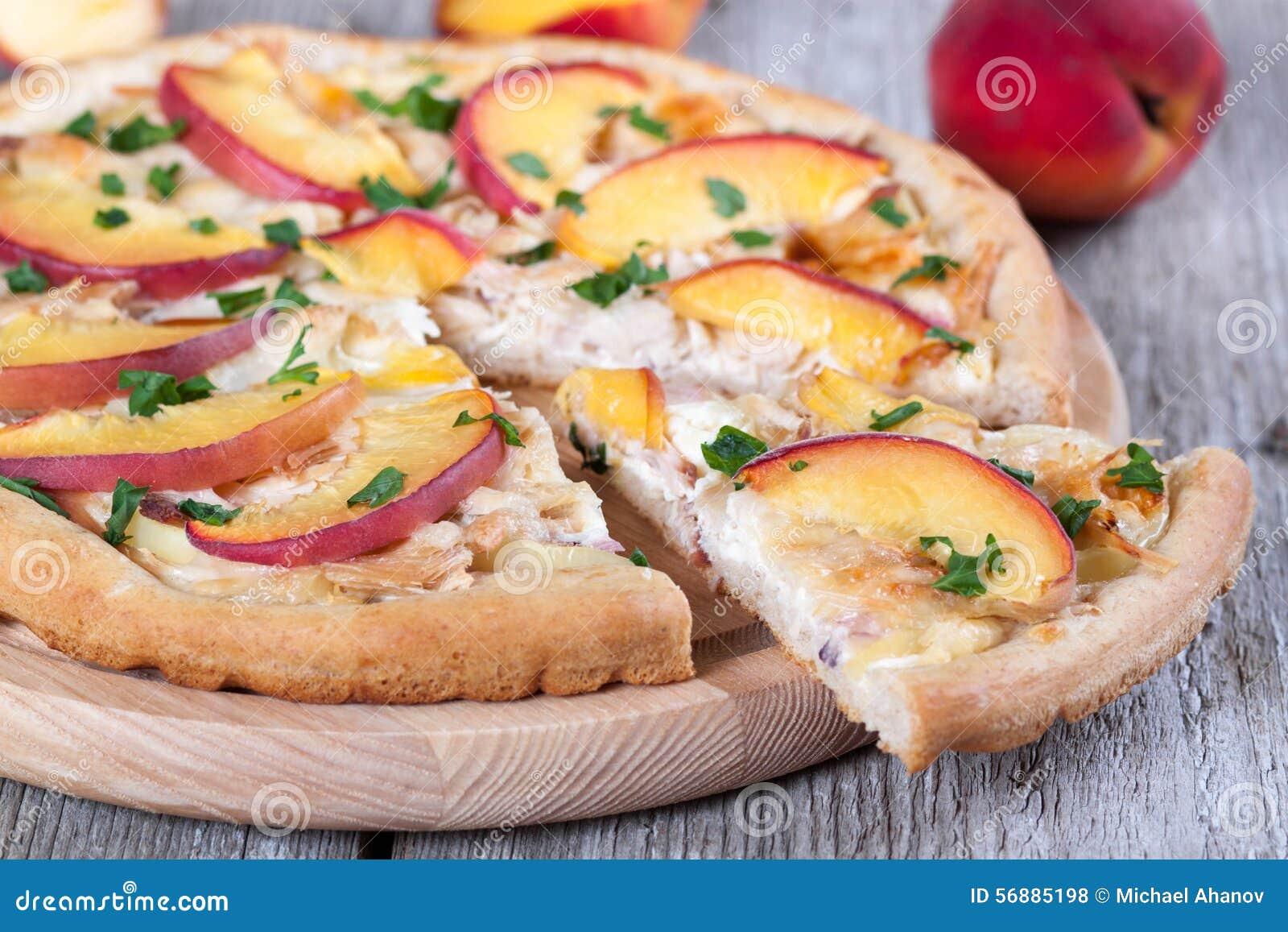 Fetta di pizza con il pollo e di pesche su un bordo di legno