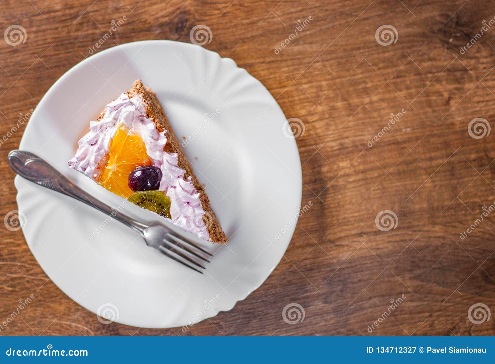 Fetta di torta di compleanno stratificata con crema con frutta in un piatto su di legno