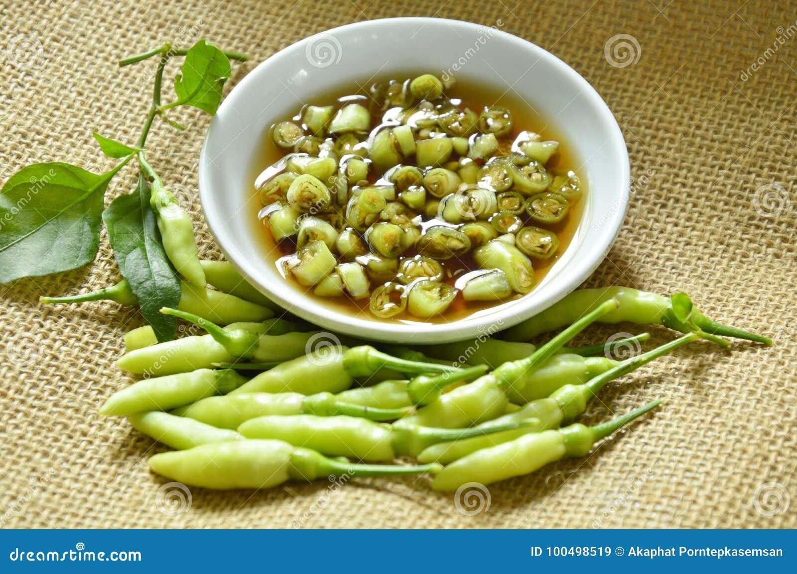 Fetta verde del peperoncino rosso e misto freschi in salsa di pesce sulla tazza
