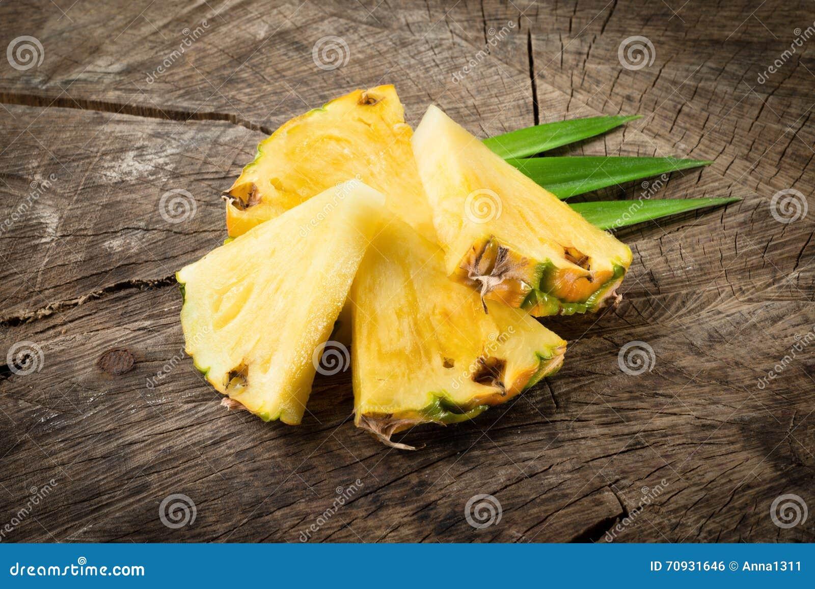 Fette dell ananas su fondo di legno