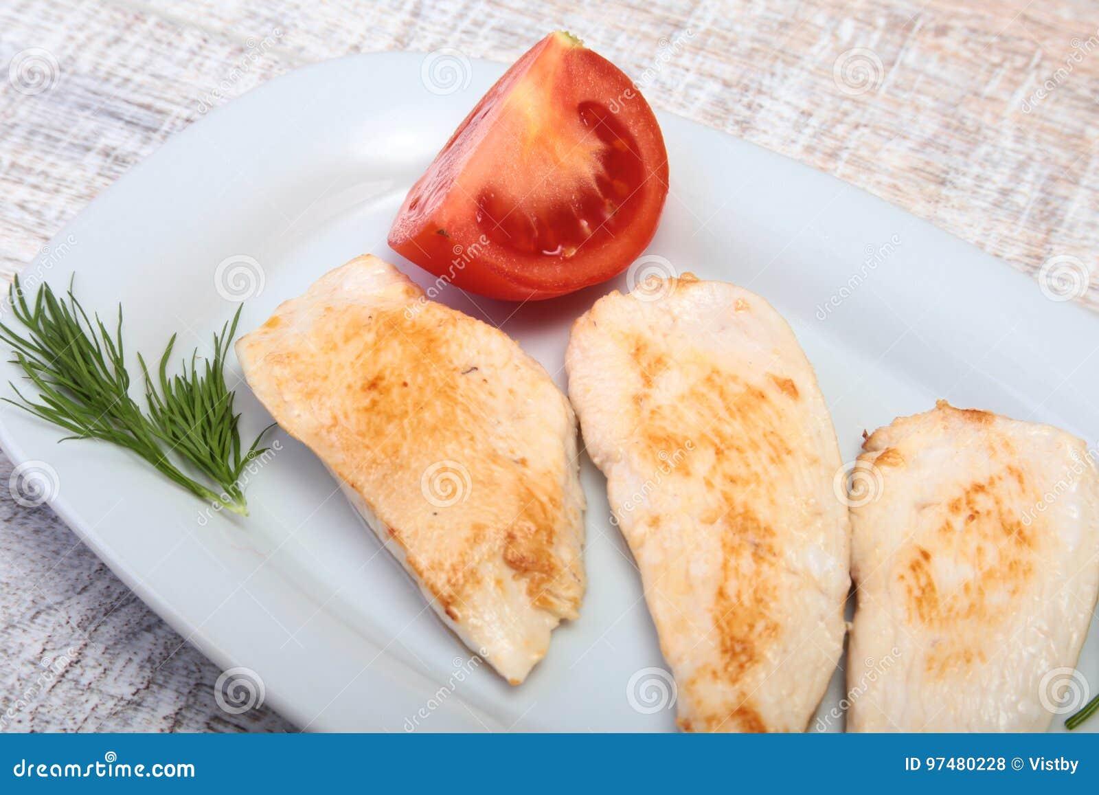 Fette di petto di pollo e di pomodoro arrostiti sul piatto bianco