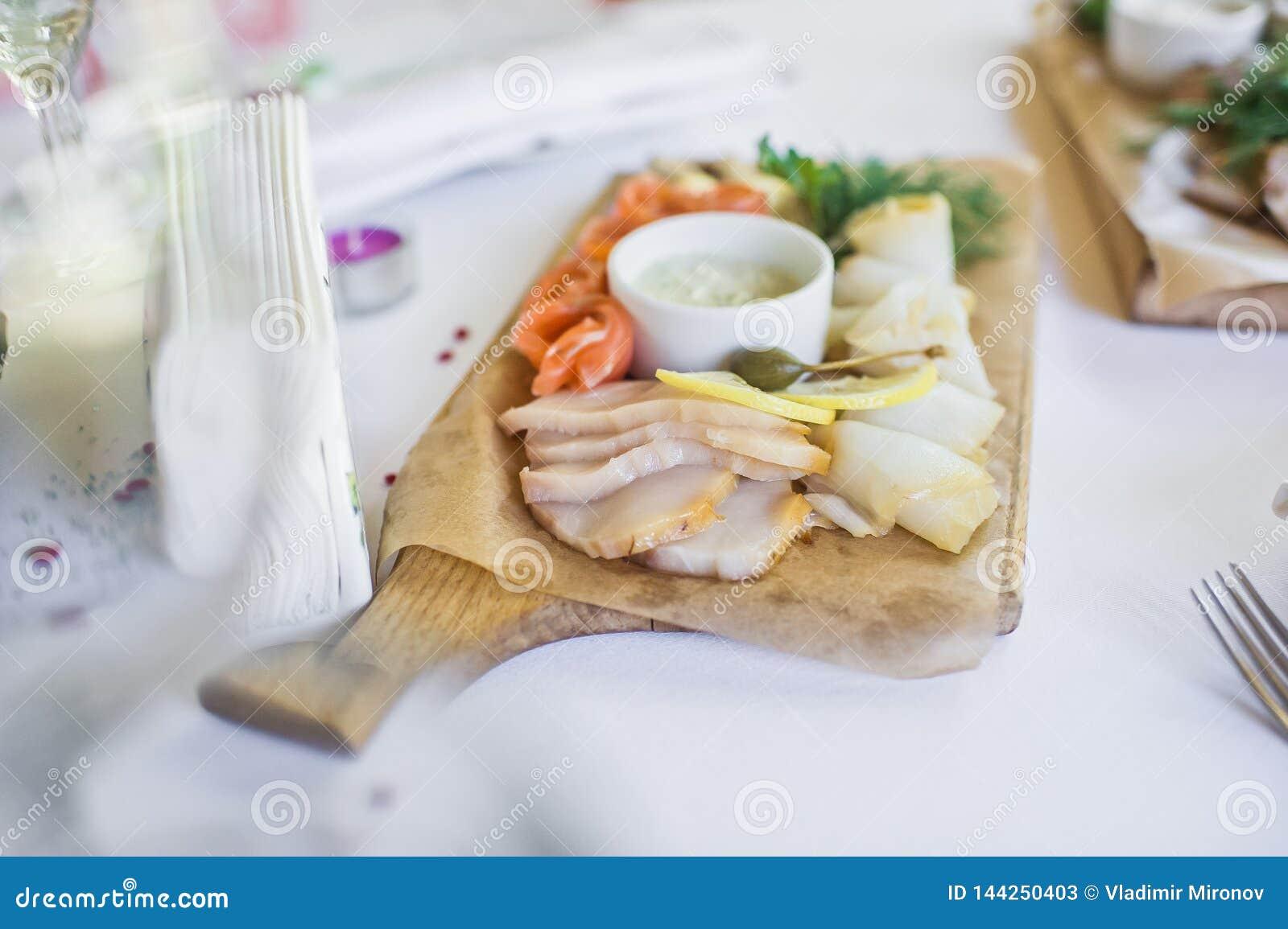 Fette di vario pesce salato - salmone, muksun, pesce oleoso sul tagliere di legno Ristorante