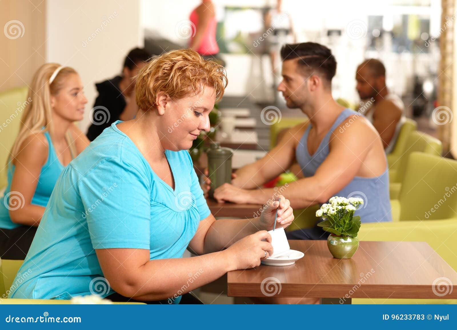 Fette Frau, die Kaffee in der Turnhalle trinkt