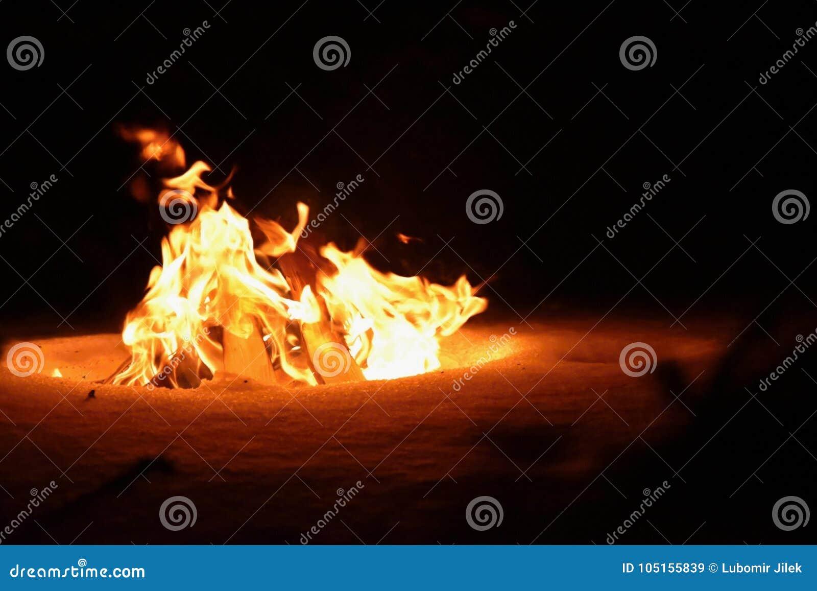 Feu Le feu brûlant en hiver sur la neige et la nuit
