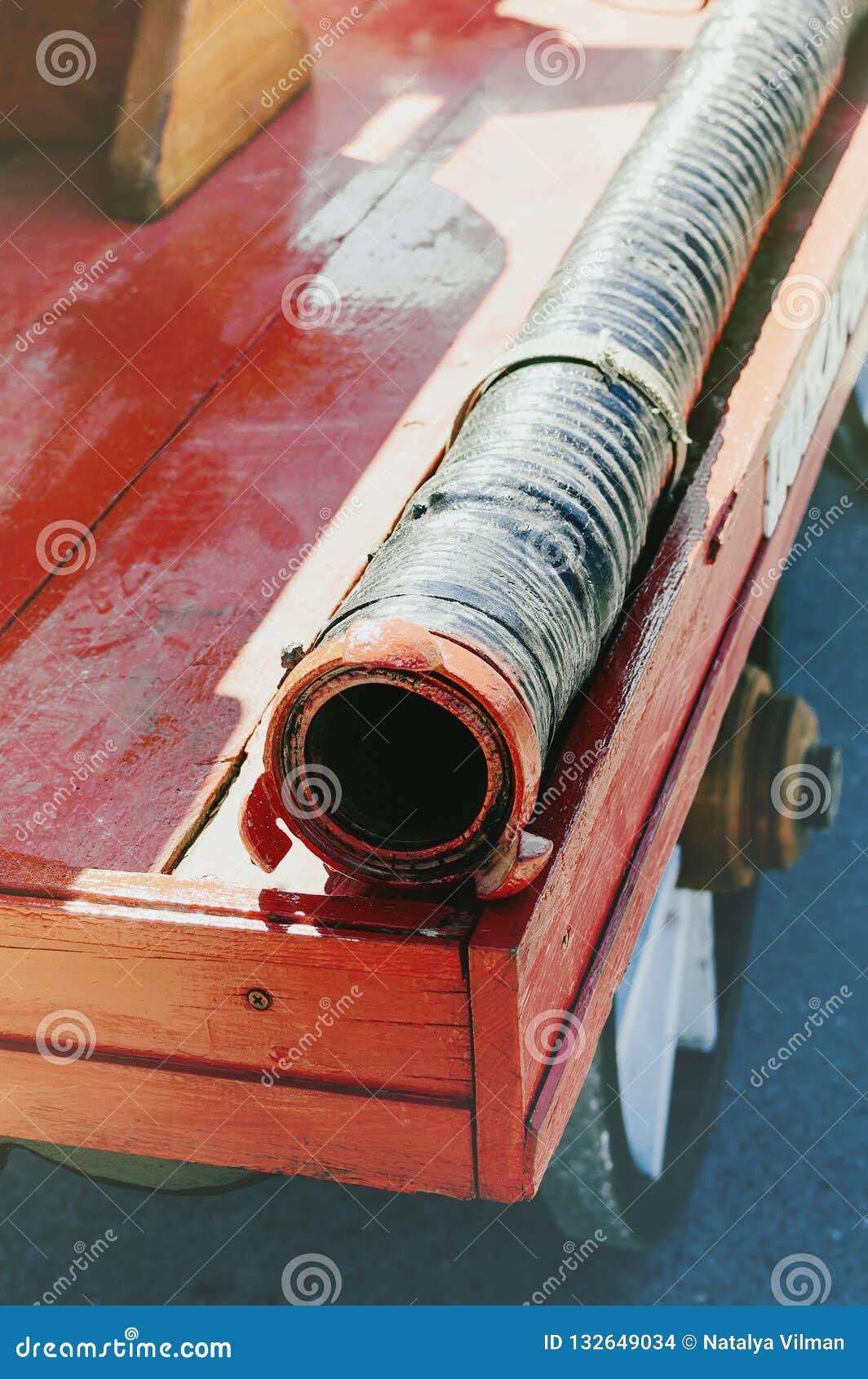 Feuerlöschschlauch auf dem hölzernen Brett eines alten roten Löschfahrzeugs Nahaufnahme
