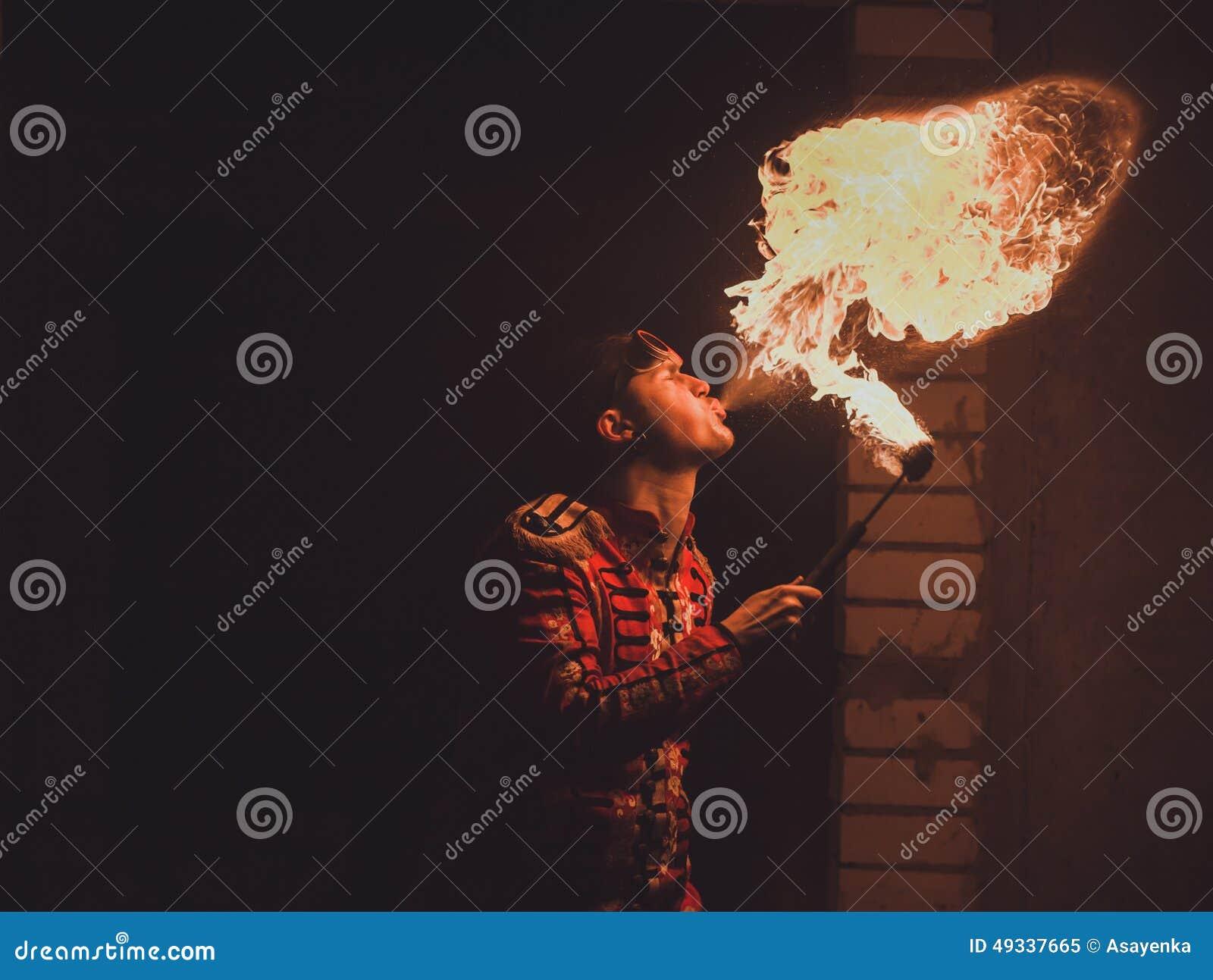 Feuershowkünstler atmen Feuer in der Dunkelheit