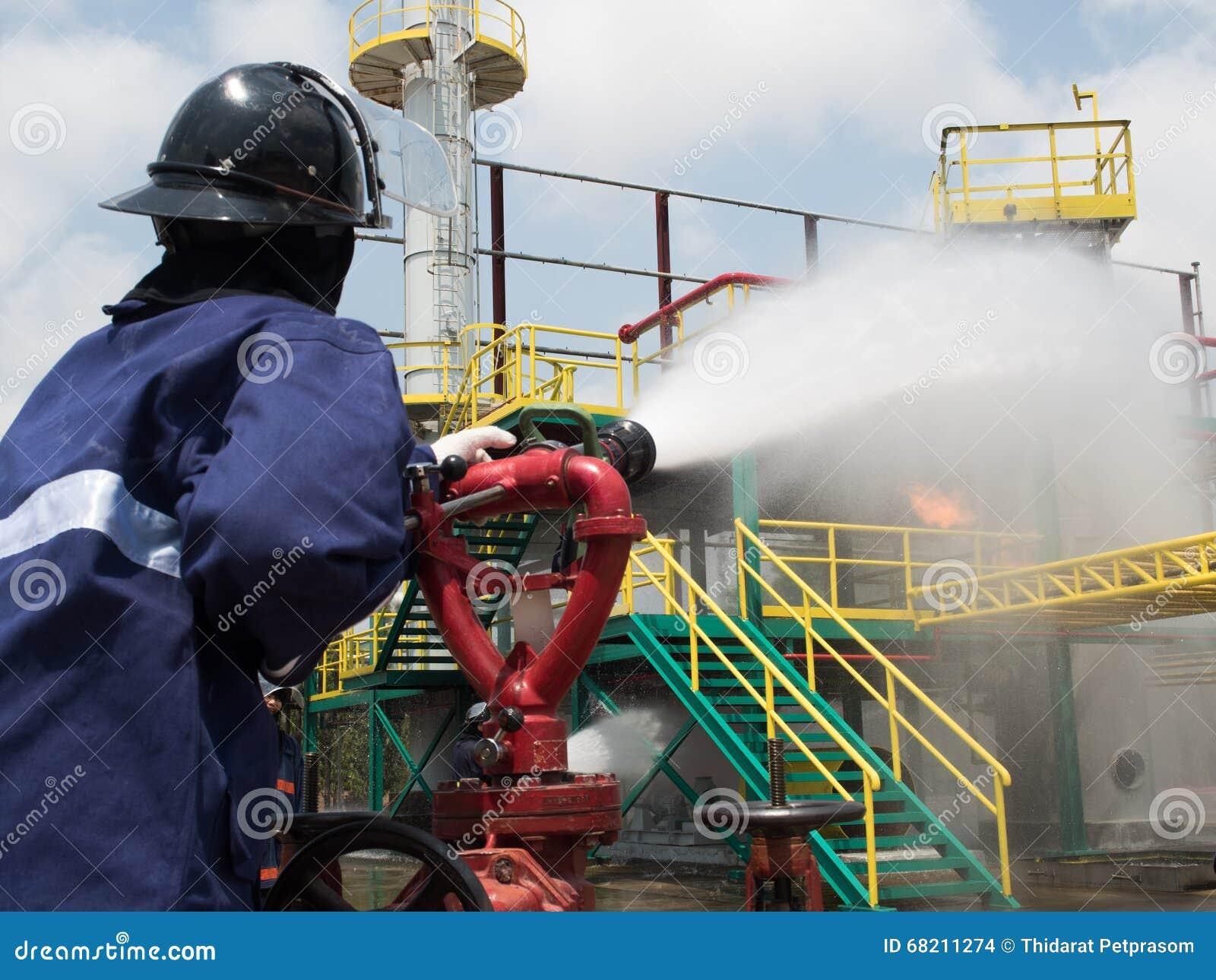 Feuerwehrmänner, die Feuer mit Druckwasser während der Schulungsübung kämpfen Feuerwehrmann, der weg einen geraden Dampf in Feuer