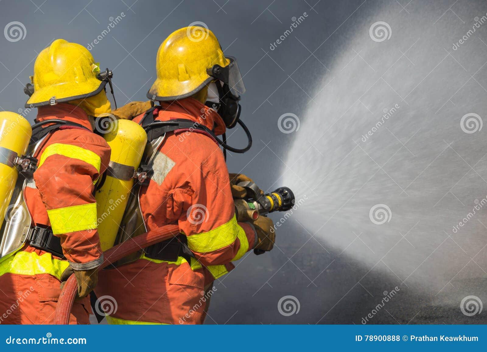 2 Feuerwehrmänner, die Wasser in der Feuerbekämpfung mit dunklem Rauche b spritzen