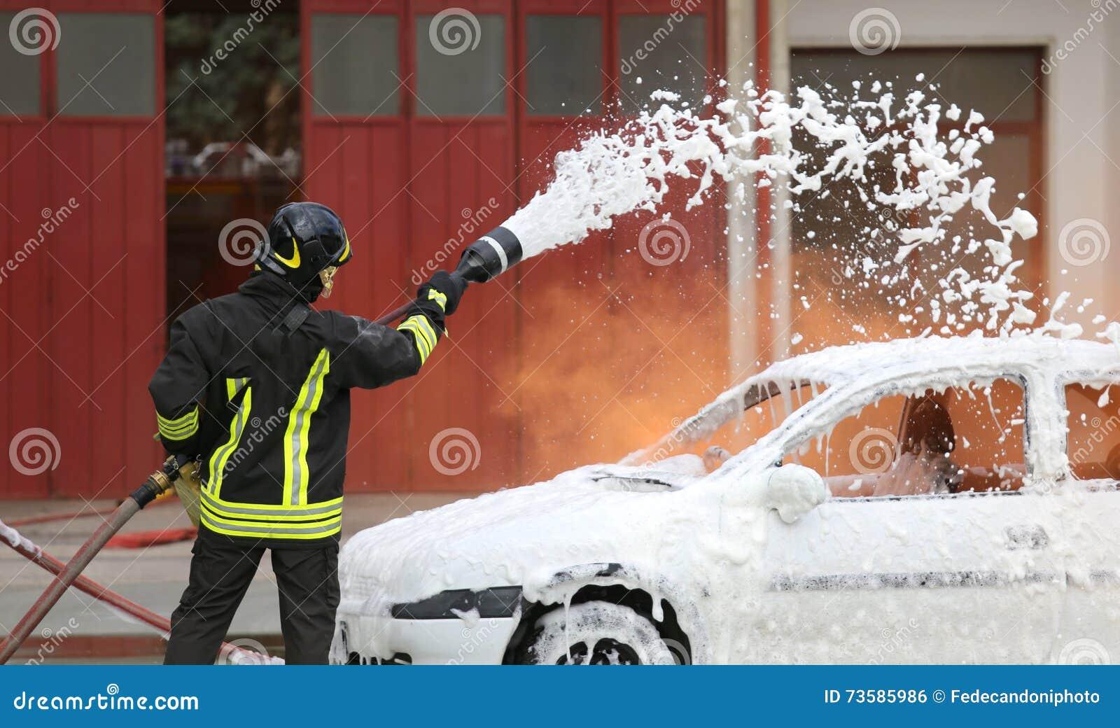 Feuerwehrmänner während der Übung, zum eines Feuers in einem Auto auszulöschen