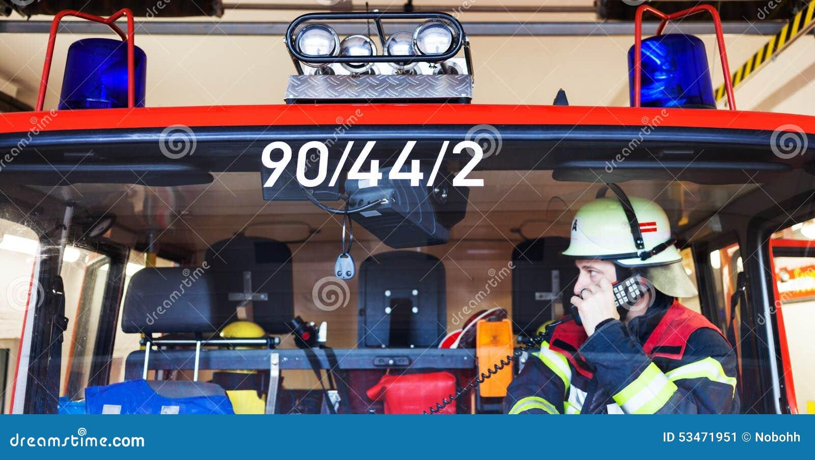 Feuerwehrmann in einem Löschfahrzeug und Funken mit Radiosatz