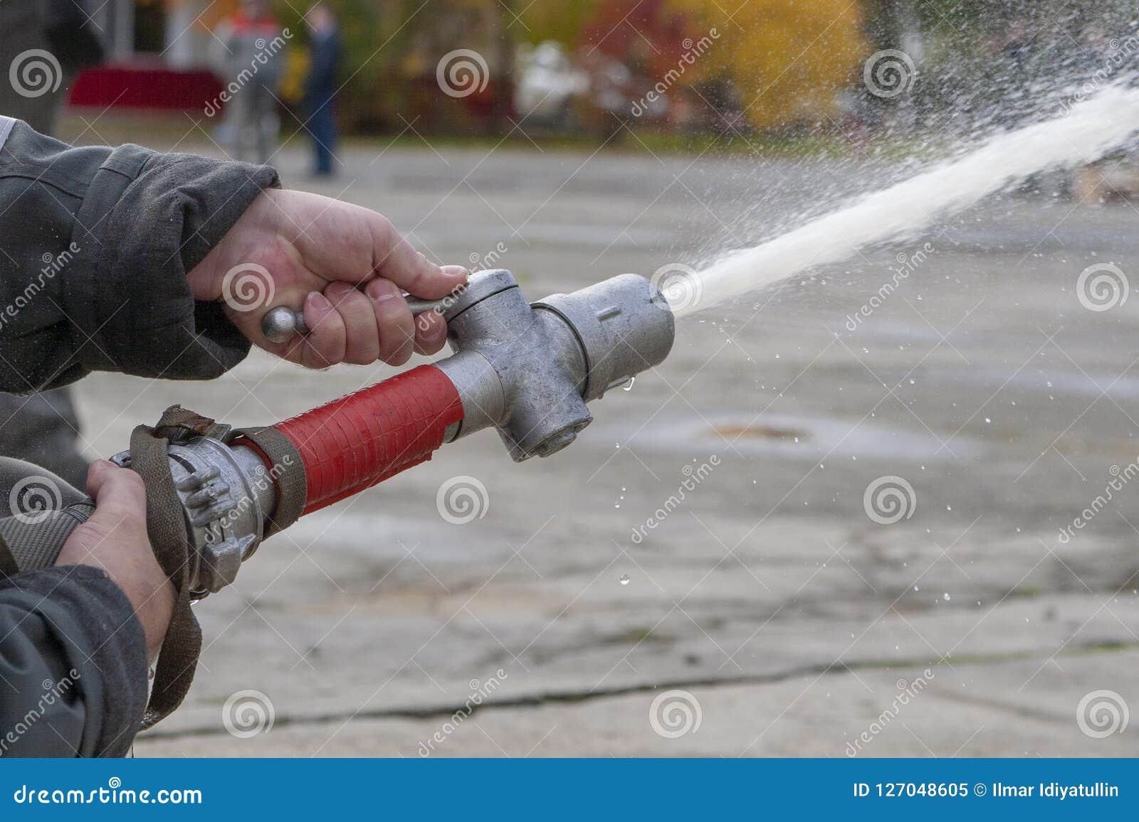 Feuerwehrmannspraywasser während einer Schulungsübung