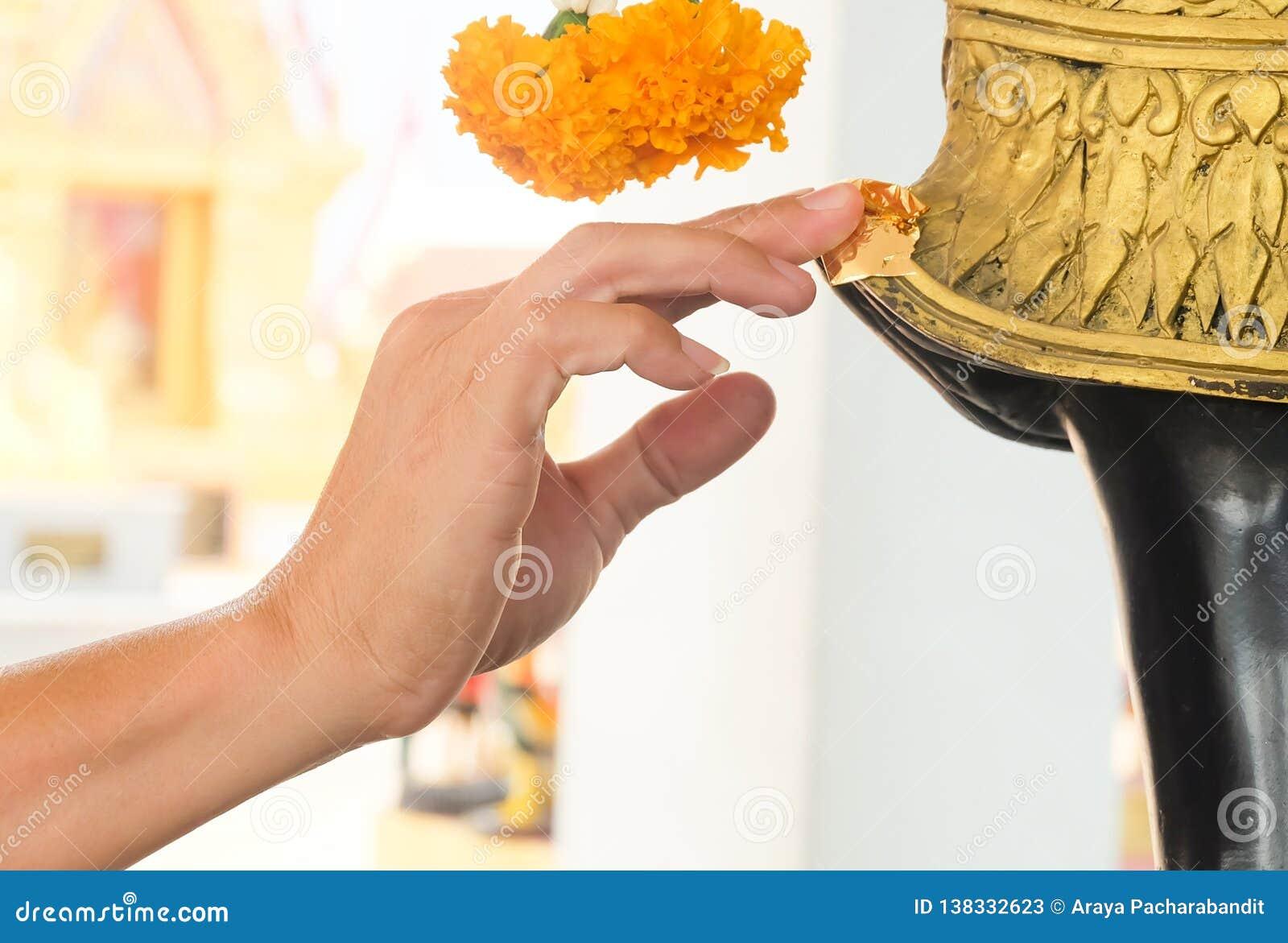 Feuille d or de dorure de main sur la statue de Bouddha