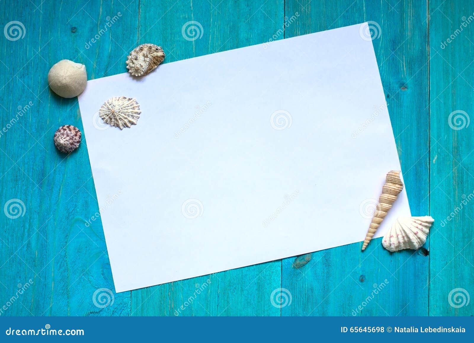 Feuille du papier blanche (l espace pour le texte), coquillages, bois bleu