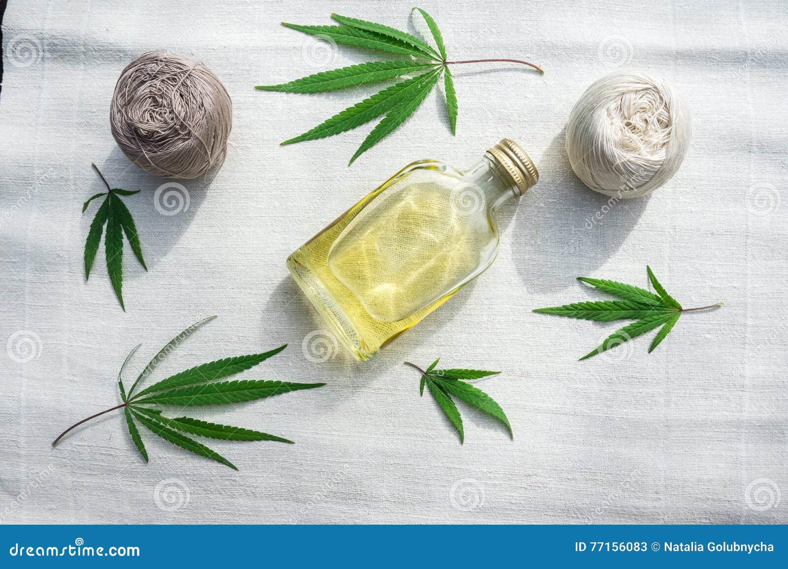 Feuilles des cannabis, boules de fil et bouteille d huile de chanvre sur le canv