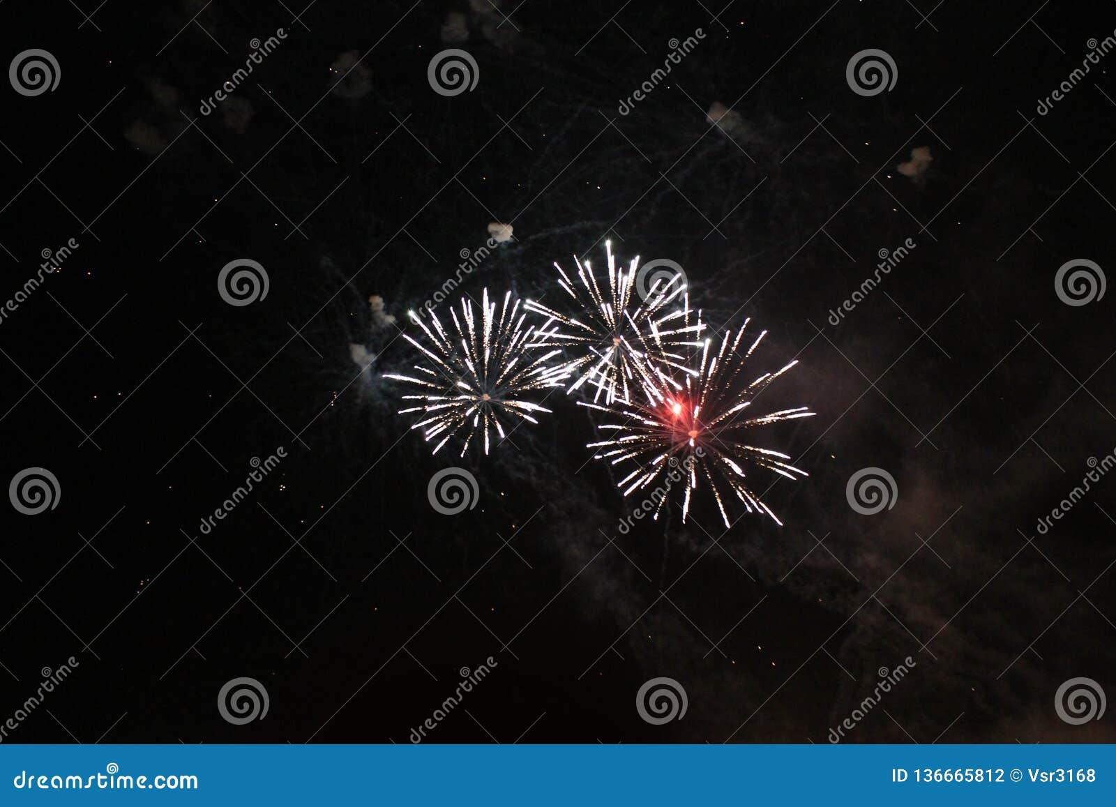 Feux d artifice salut Fond de ciel un trio des lumières de scintillement rouges, vertes et bleues lumineuses dans le ciel nocturn