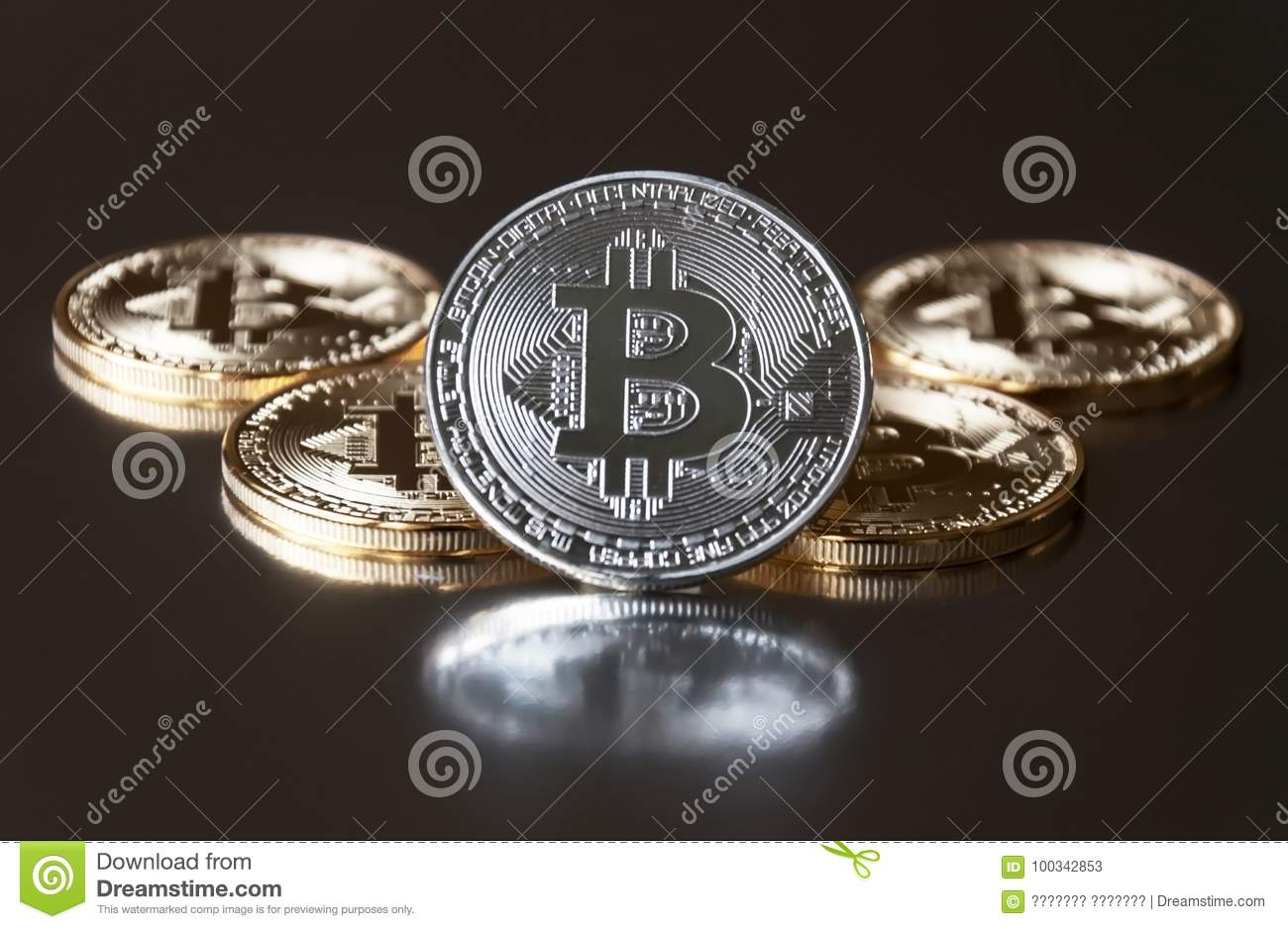 A few gold and silver coins bitcoin lie or stay on edge on a dark background. The concept of crypto currency.
