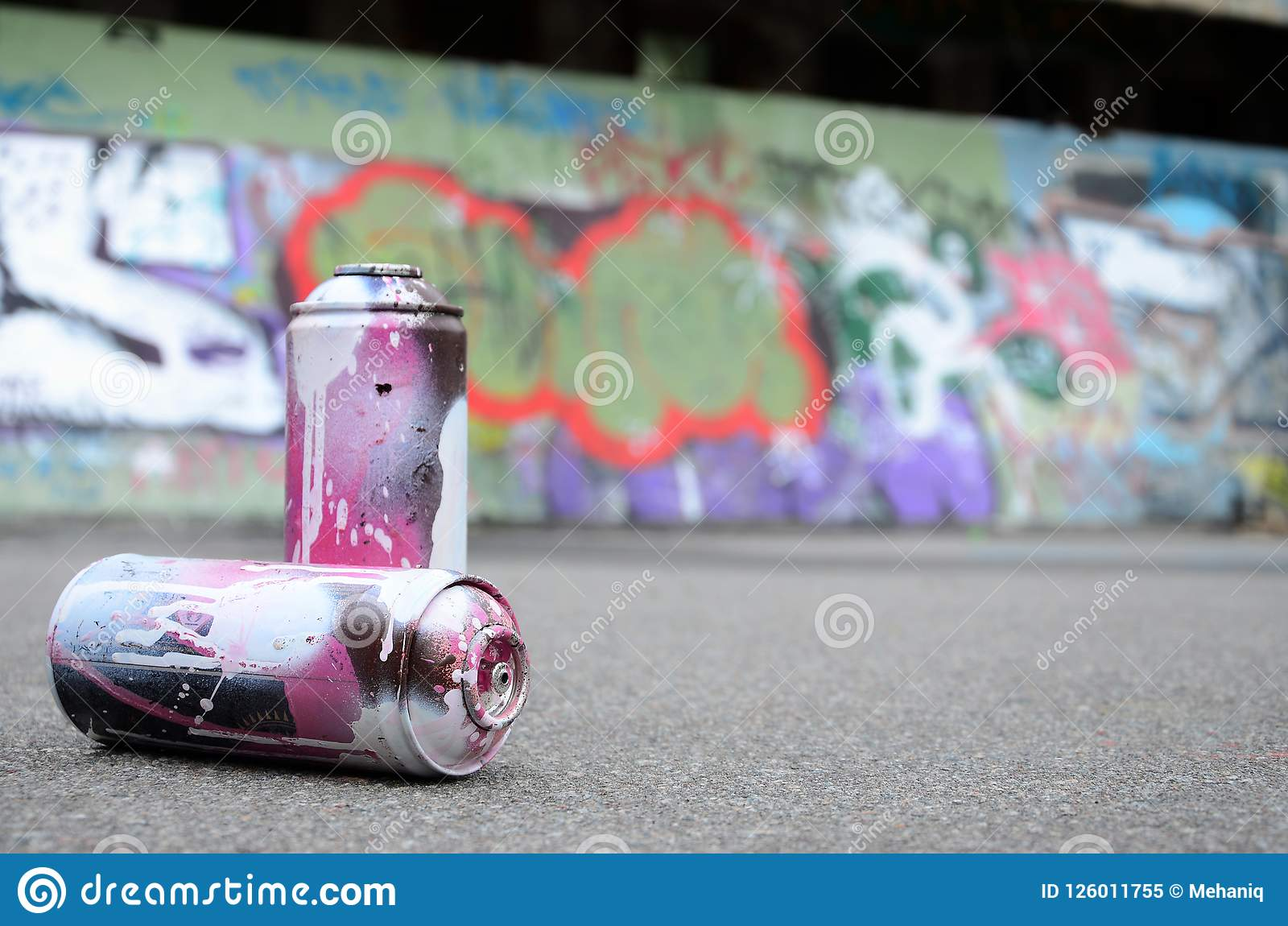 A few used spray cans with pink and white paint lie on the asphalt against the background of a painted wall in colorful graffiti