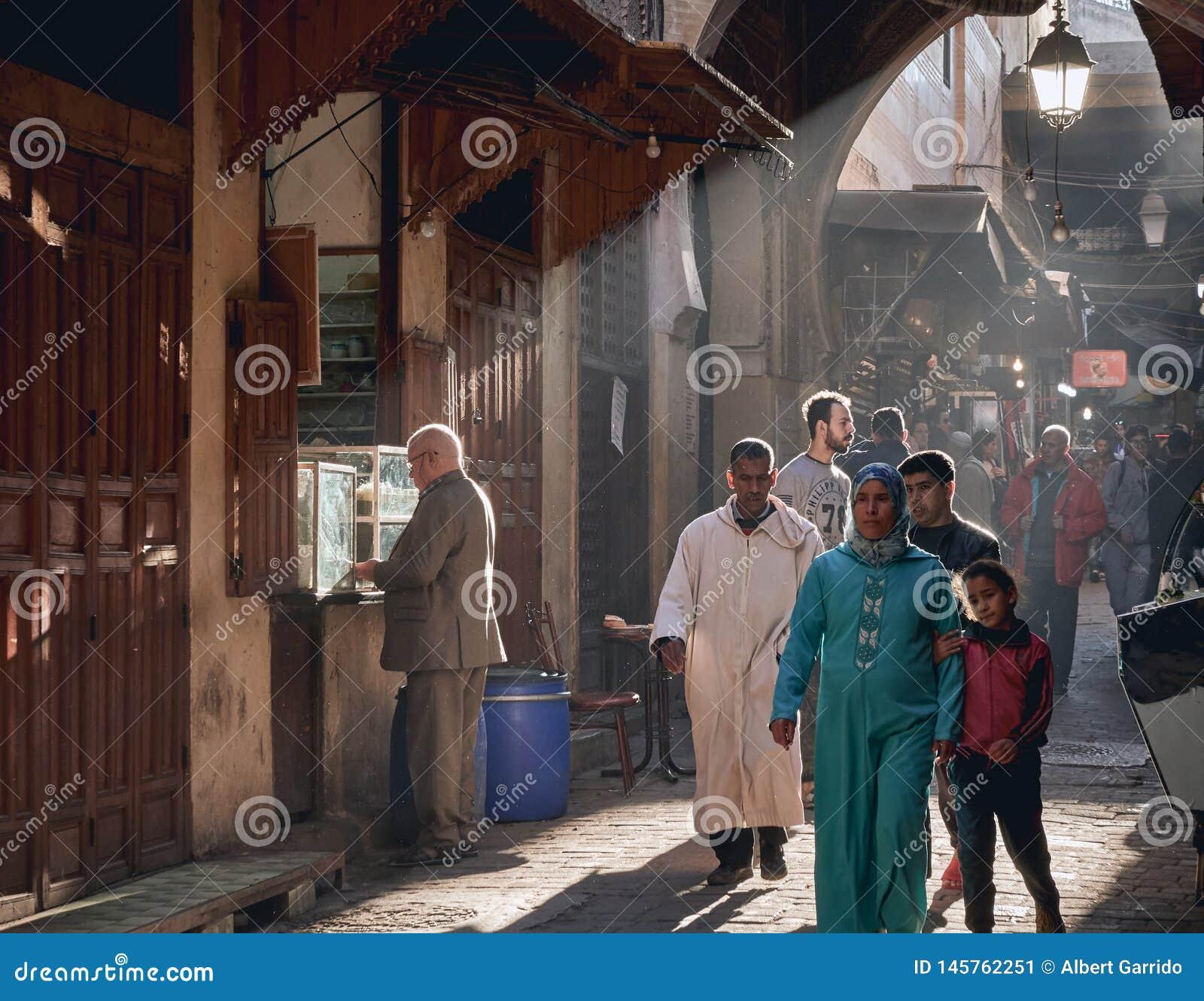 Fez Maroko, Grudzień, - 07, 2018: Marokańska dama z jej córki odprowadzeniem przez przejścia fez Medina z promieniami światło